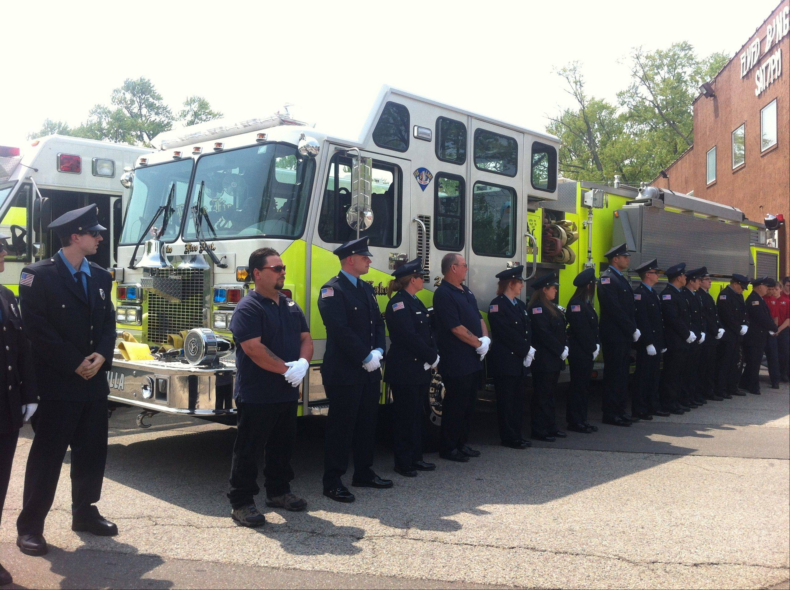 Firefighters stand at attention during the dedication ceremony for a firefighter memorial in Fox Lake Sunday.