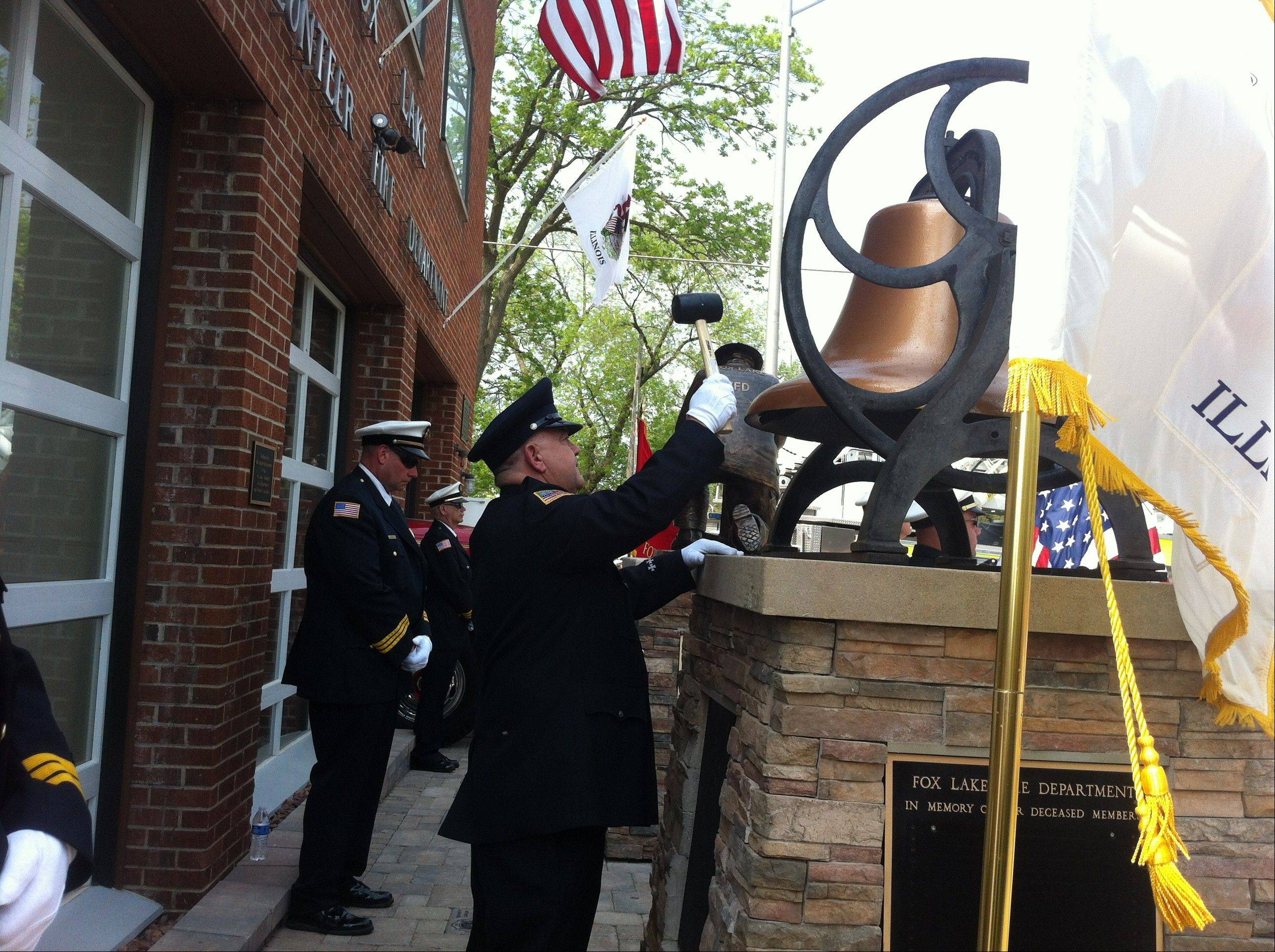 Firefighters ring a memorial bell recognizing the names of each former firefighter as a memorial to their legacy is dedicated Sunday.