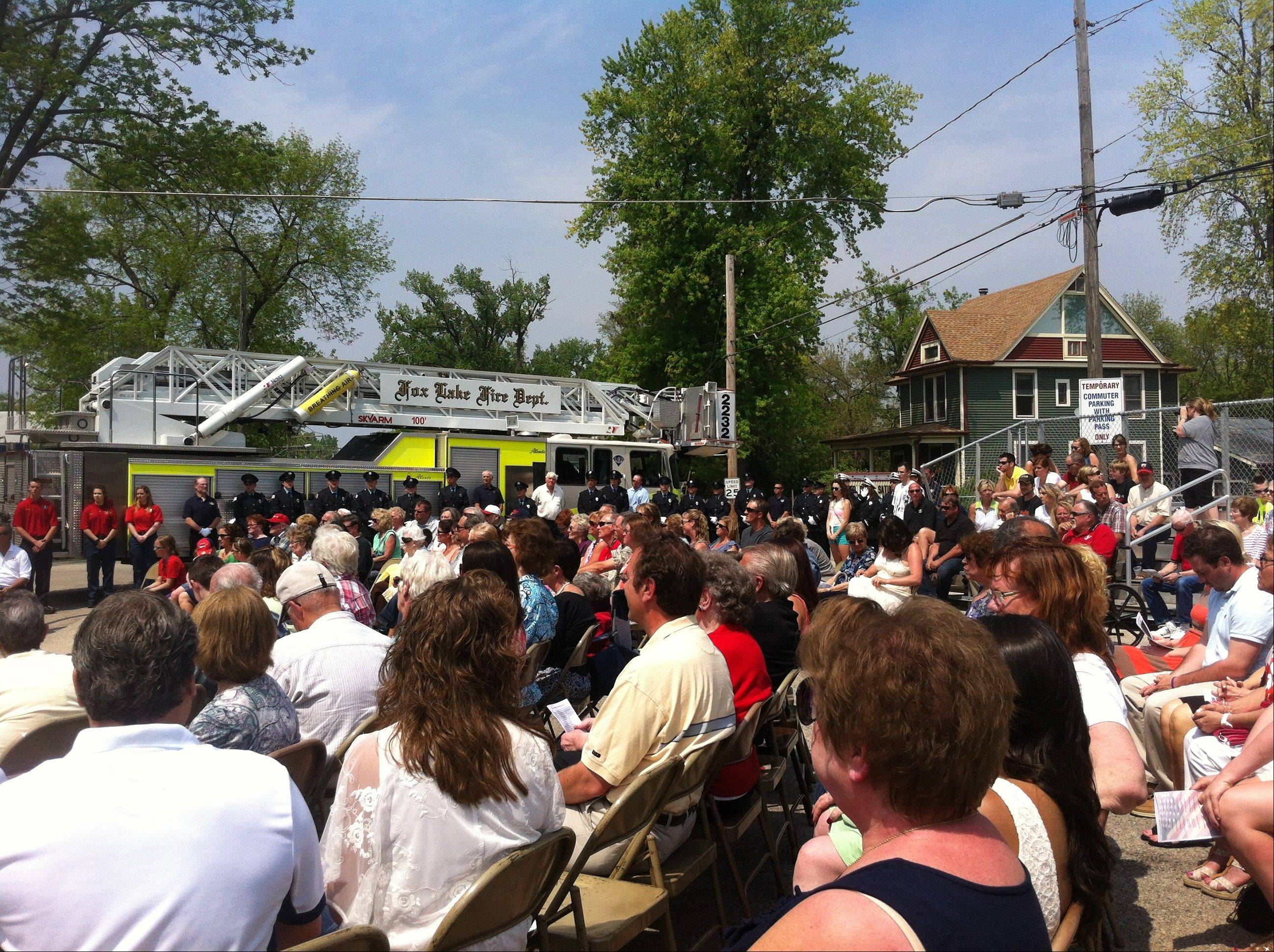 A crowd of family and friends watch officials unveil a firefighter memorial in Fox Lake Sunday.