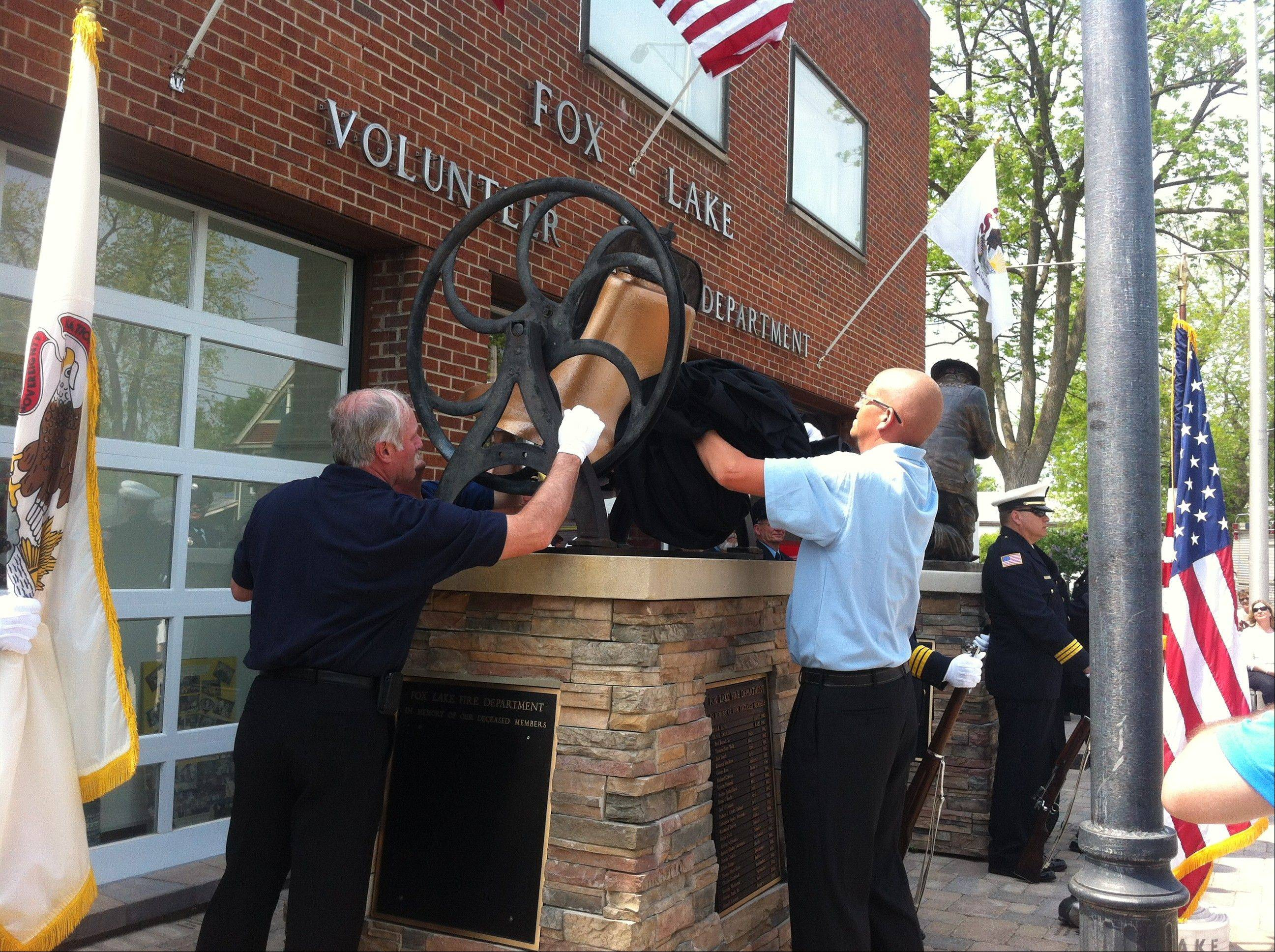 Volunteer Fox Lake firefighters unveil a memorial to former firefighters Sunday afternoon.