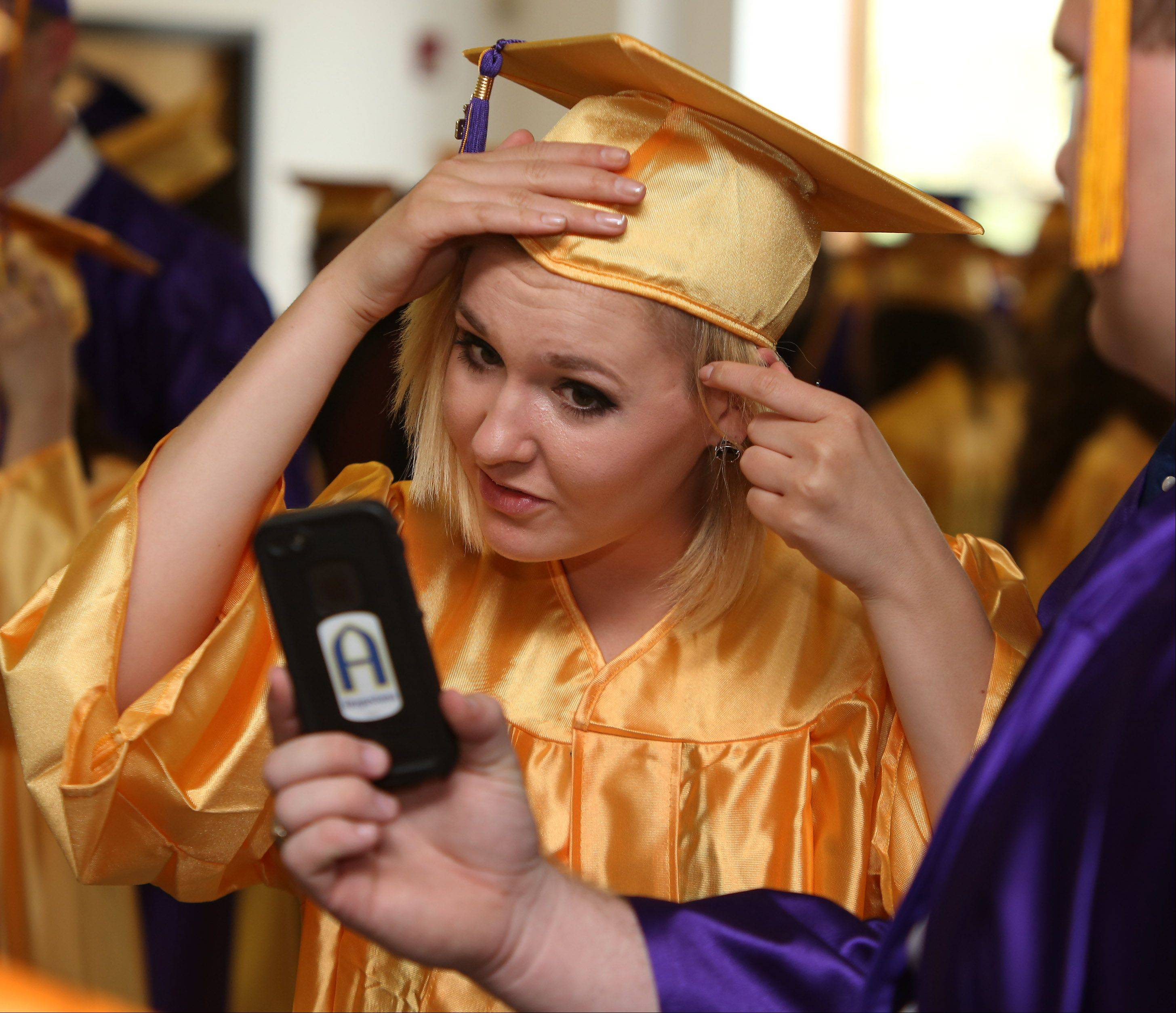 Malia Lakatos uses an iPhone to see herself as she fixes her hair before the Wauconda High School graduation at Quentin Road Bible Baptist Church on Sunday in Lake Zurich. There were 341 graduating seniors for the 97th annual commencement ceremony.