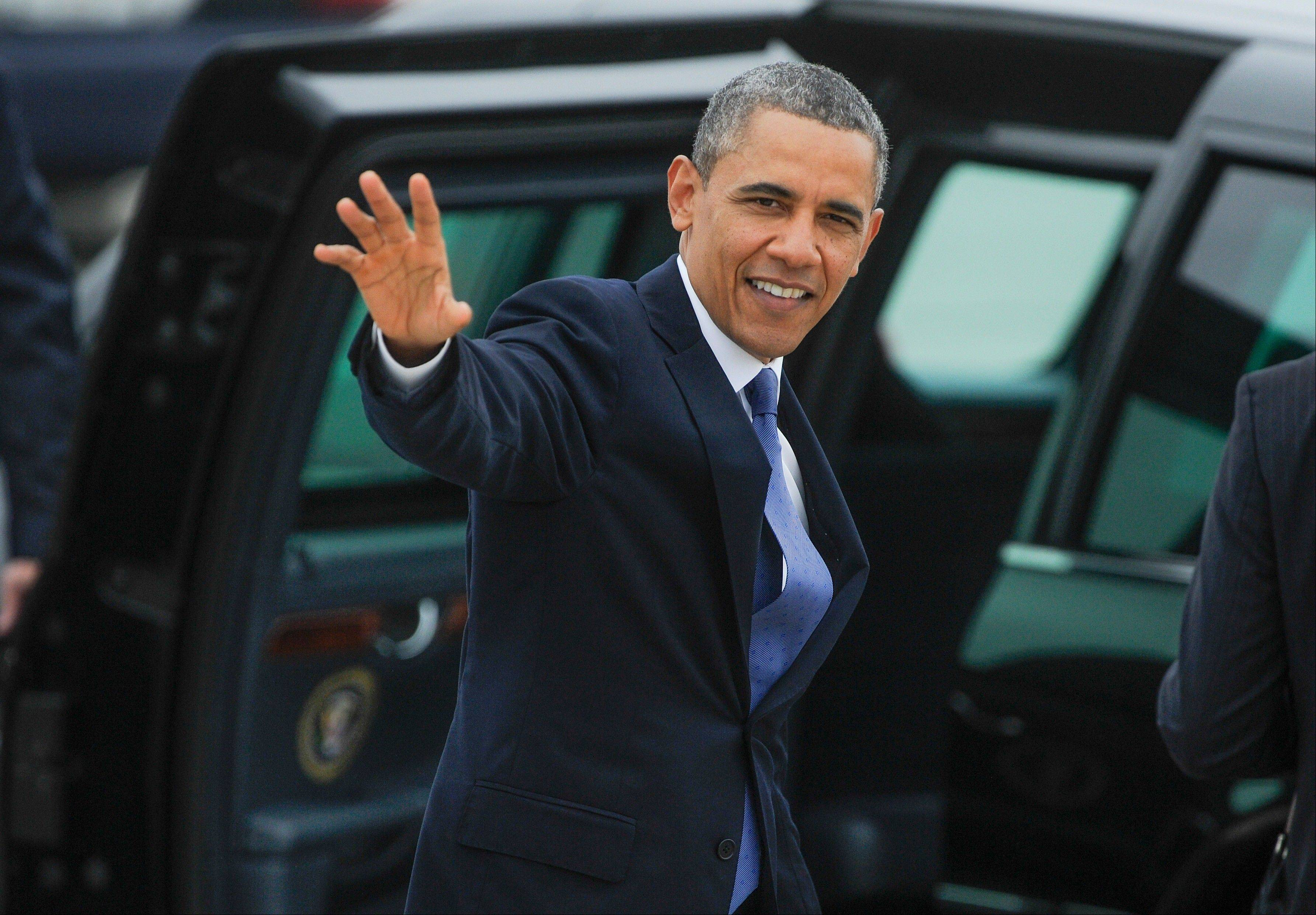 President Barack Obama waves to a crowd gathered at Hartsfield-Jackson International Airport on his way to give the commencement speech at Morehouse College Sunday in Atlanta.