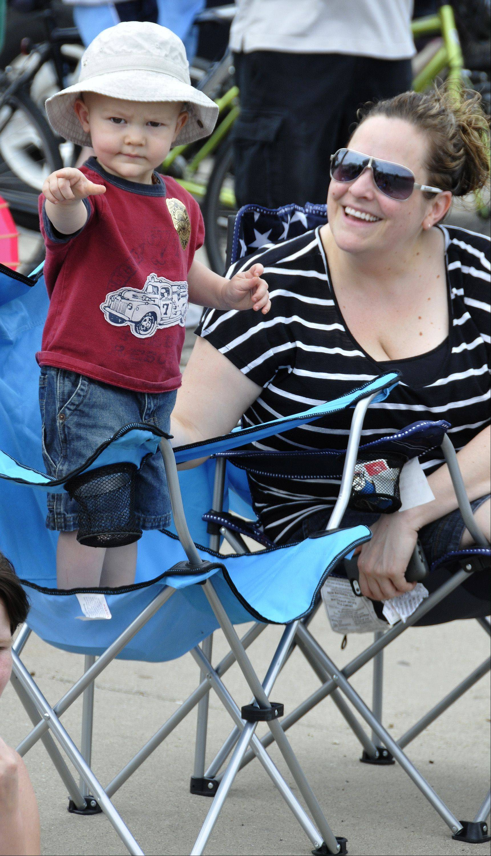 With the help of a chair, Jackson Suter spots the parade coming up Main Street in Lombard Sunday for his mother Jenn Suter, right.