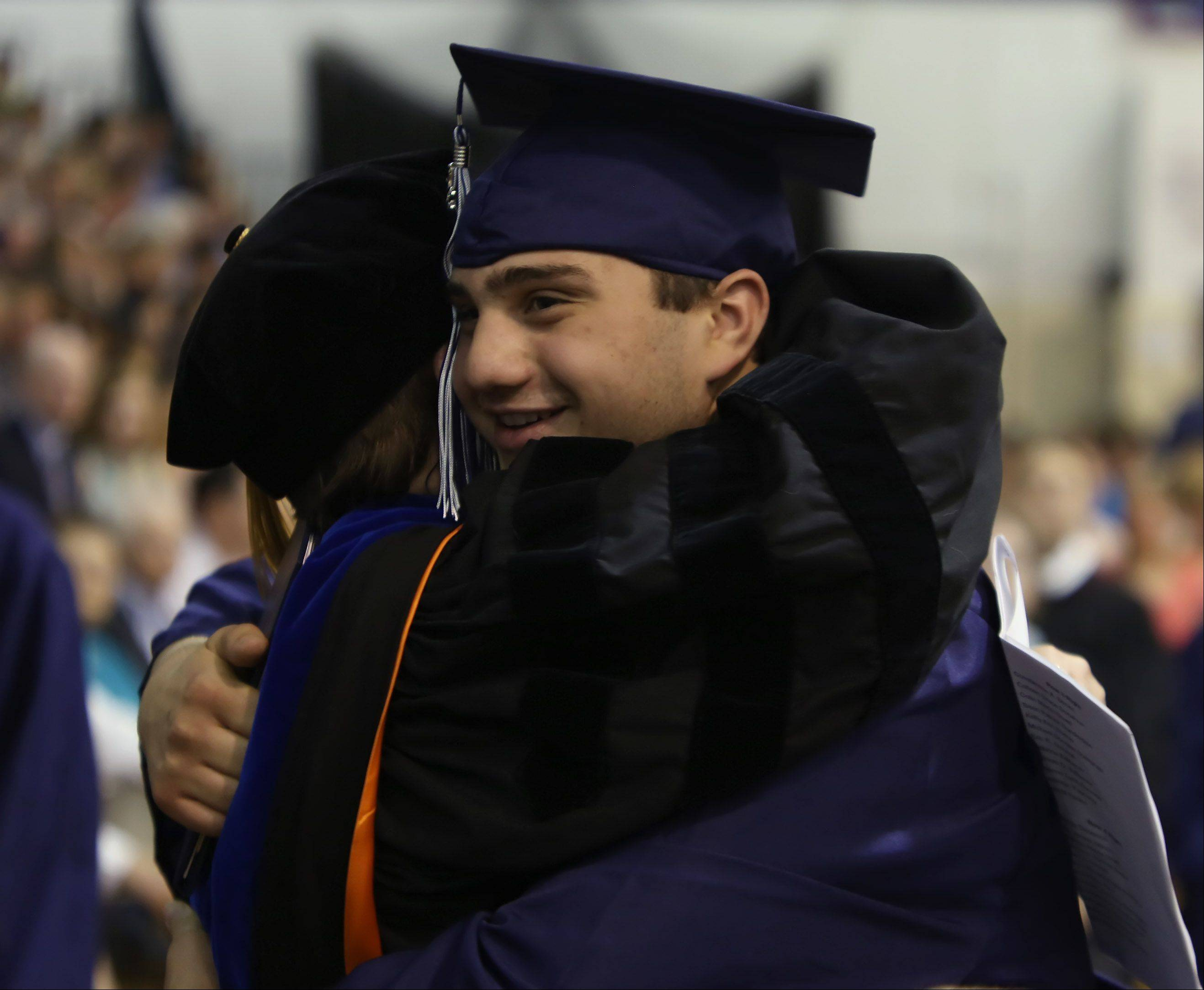 Dean Dimitri hugs Dr. Deb Scerbicke after receiving his diploma during the St. Viator graduation ceremony Sunday at the high school in Arlington Heights.