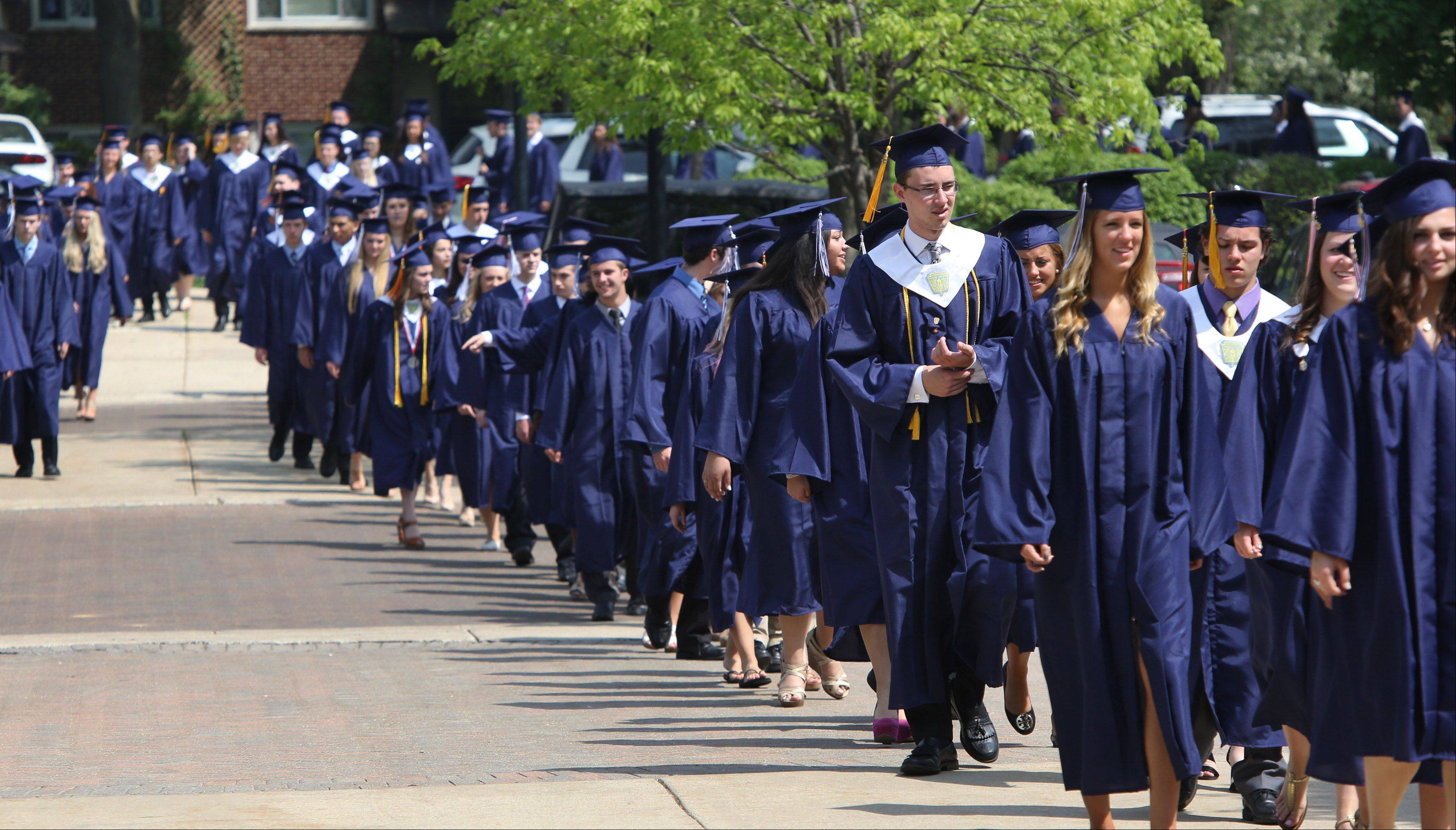 Graduating seniors begin their procession outside as they walk in the front door during the St. Viator graduation ceremony Sunday at the high school in Arlington Heights.