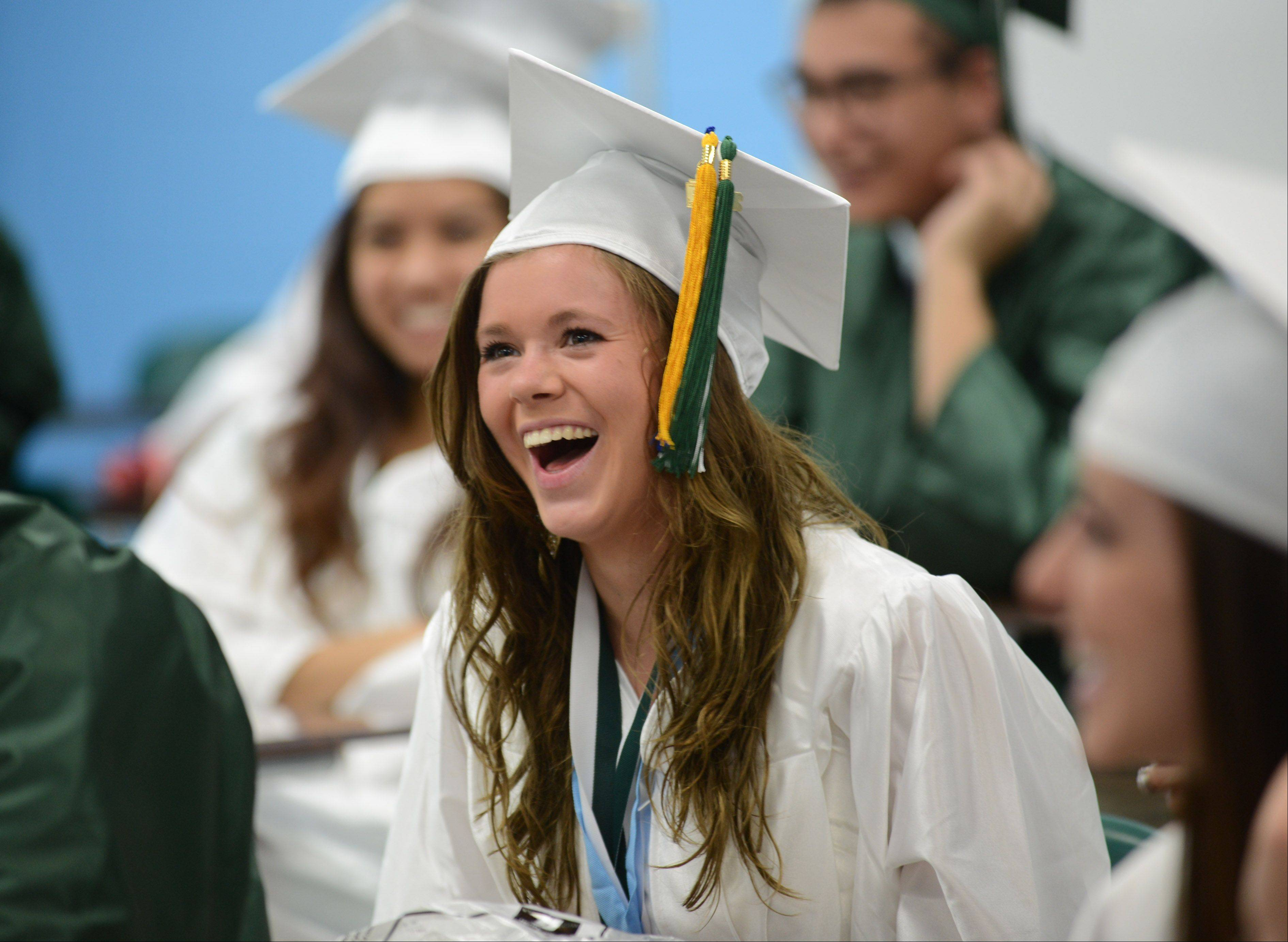 Grayslake Central High School senior Silvie Lehtis shares a laugh with fellow graduates before the start of Sunday's graduation ceremony at the school.