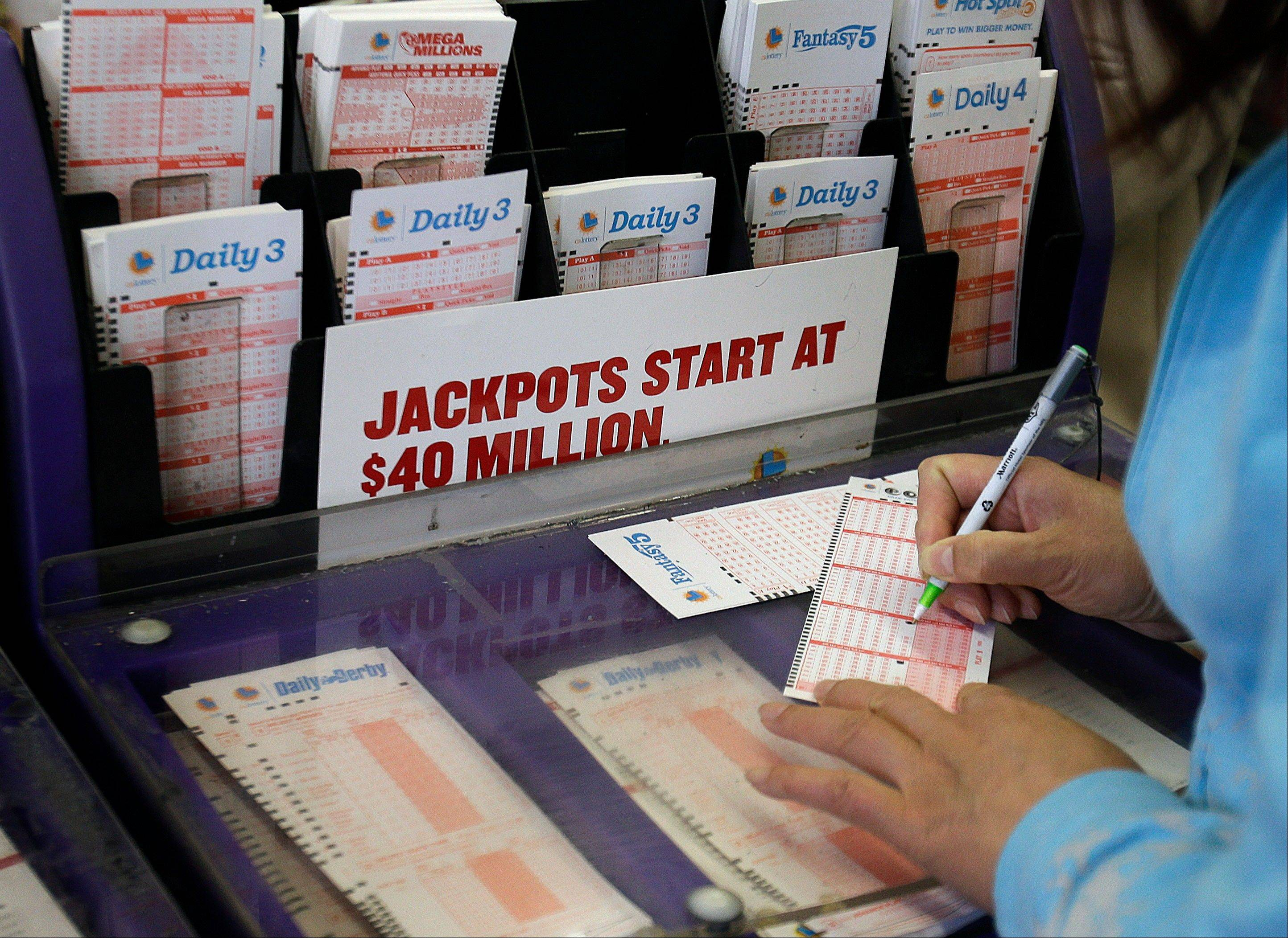 A woman prepares to choose her numbers on a lottery ticket Saturday in Oakland, Calif. The record Powerball jackpot has climbed to $600 million, and lottery officials say the winning ticket was sold in Florida.