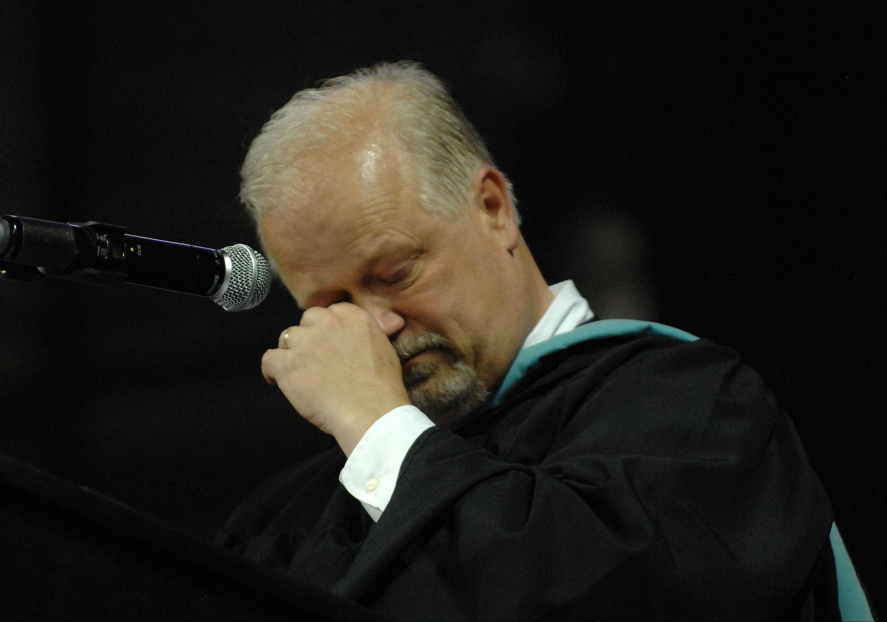 Chuck Bumbales gets choked up as he offers his last welcoming speech as principal of Hampshire High School during their graduation ceremony Saturday at the Sears Centre in Hoffman Estates. He'll be leaving at the end of the school year.