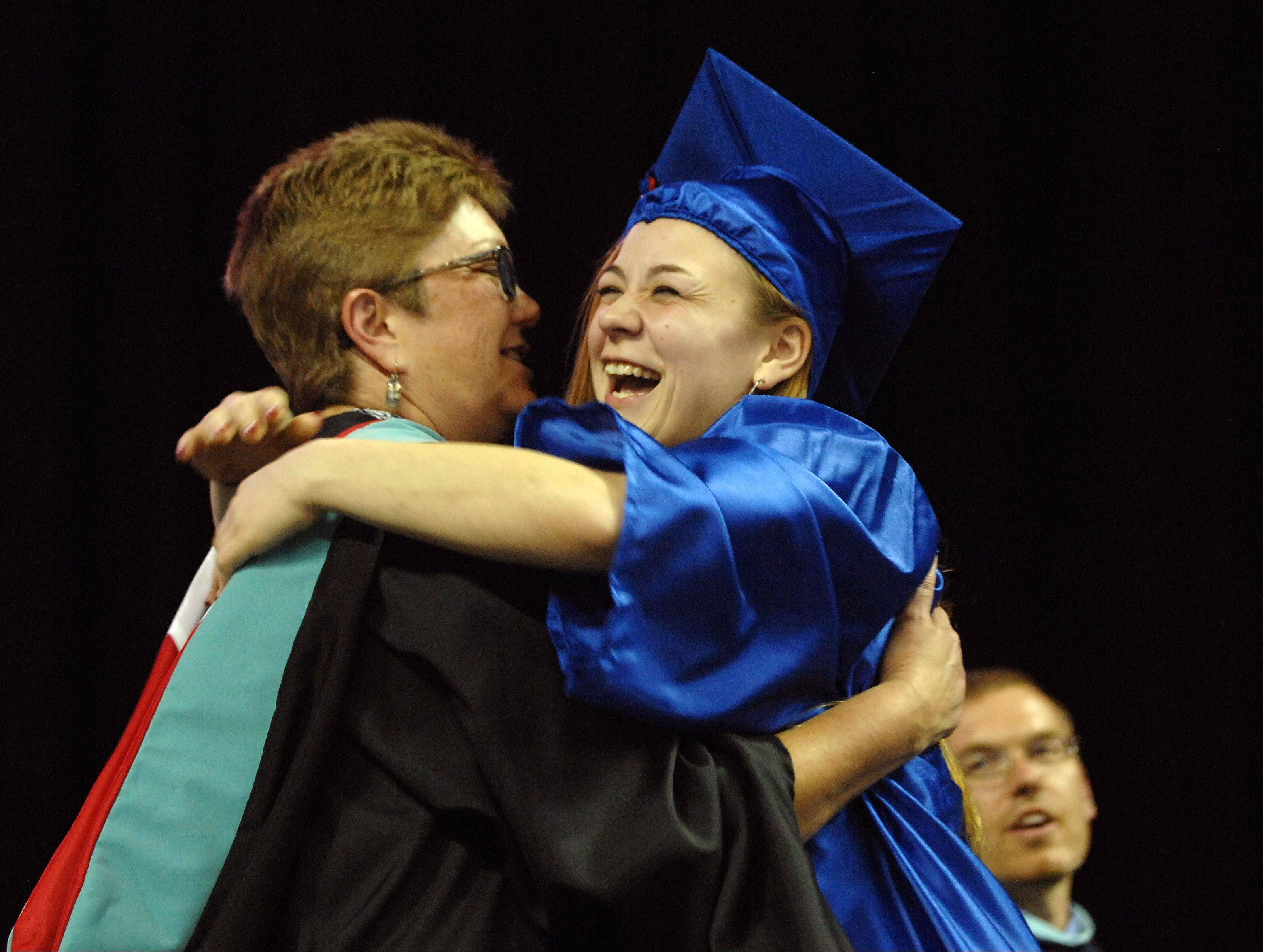 Emily Weyers gets a hug from principal Lynn McCarthy during Dundee-Crown's graduation ceremony Saturday at the Sears Centre in Hoffman Estates.