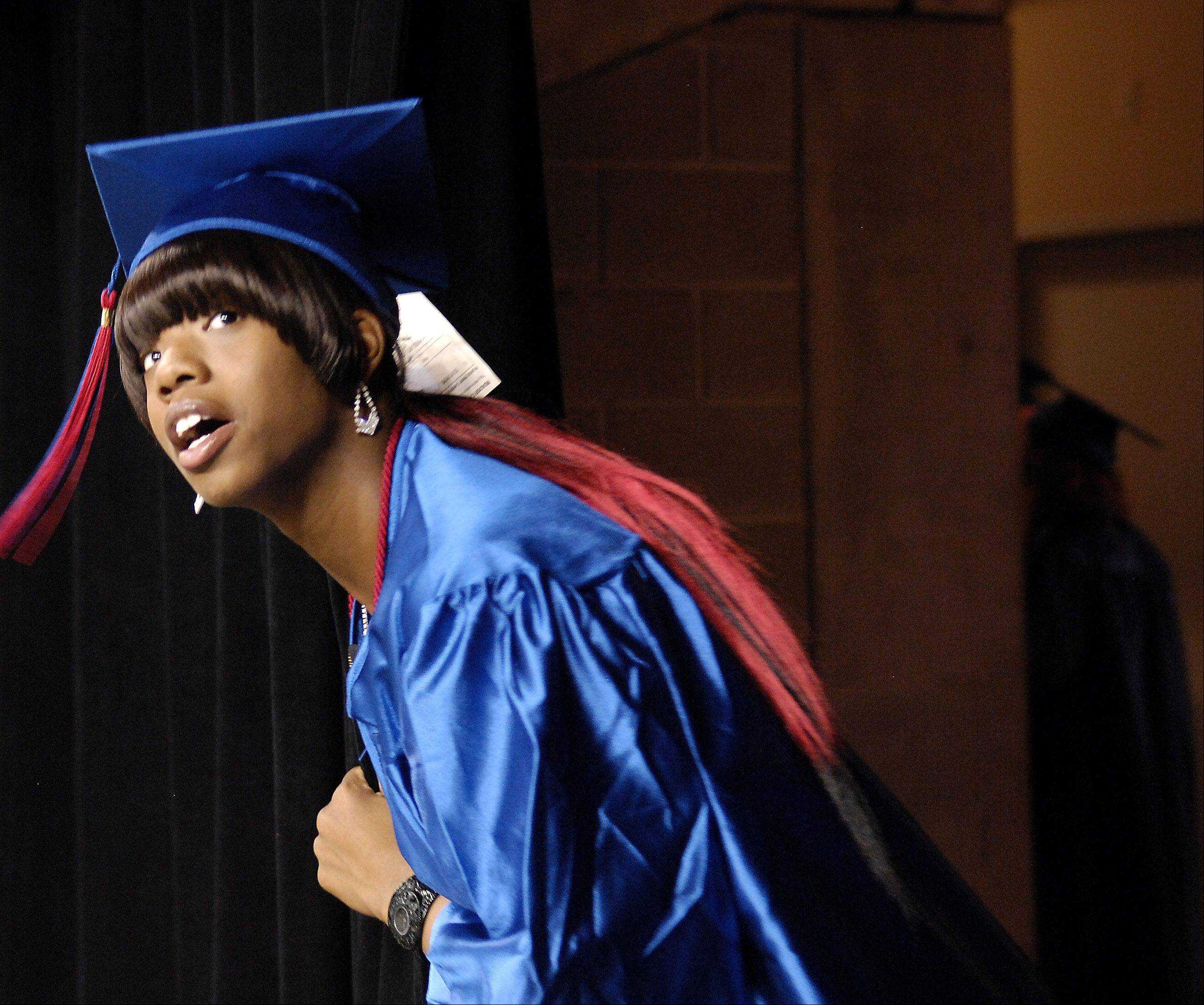 Shameeka Bramlett peeks her head out of the tunnel to look for her family before the start of Dundee-Crown's graduation ceremony Saturday at the Sears Centre in Hoffman Estates.