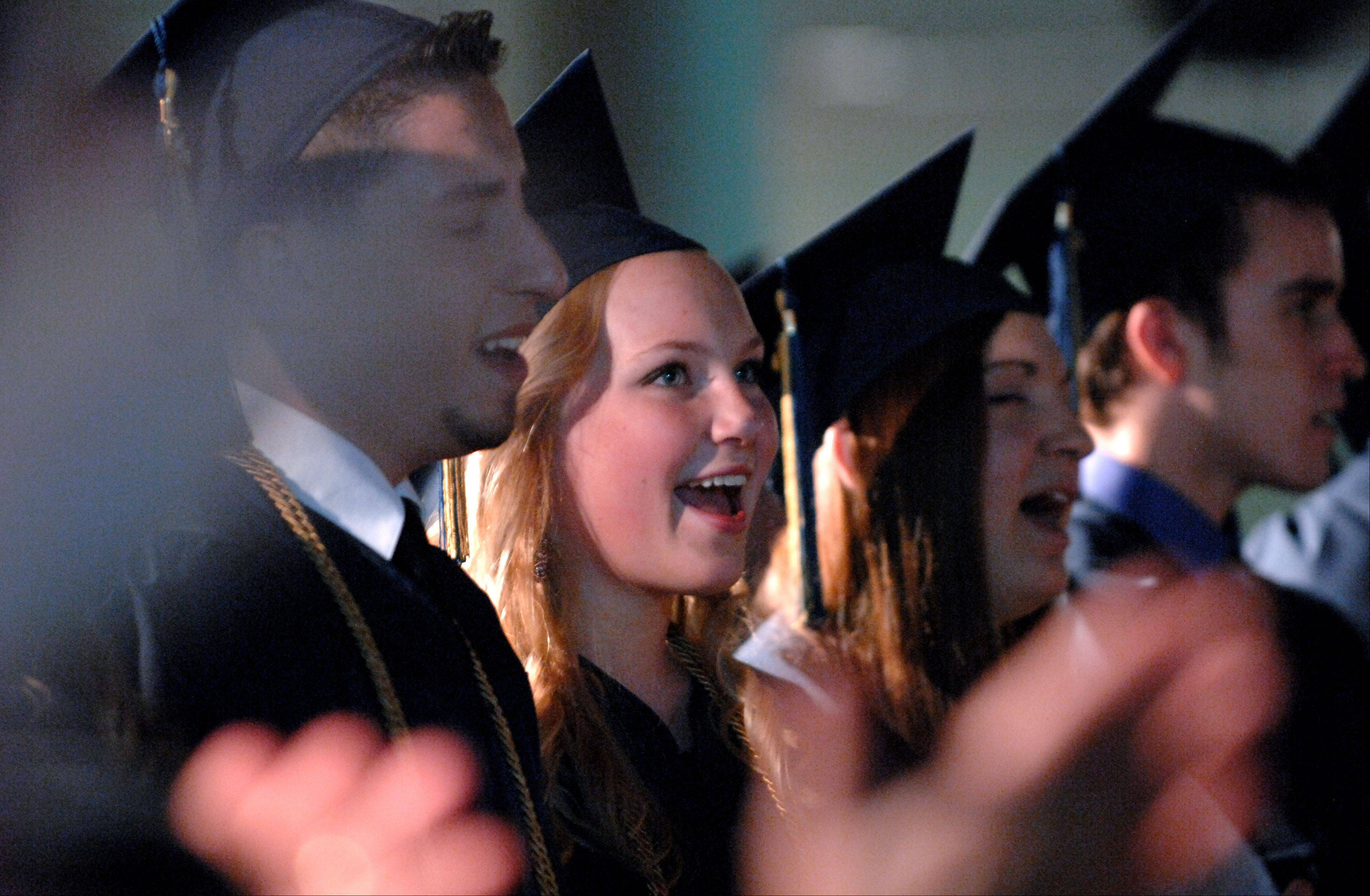 Cayla Aronsen and her fellow seniors sing a worship song during the Harvest Christian Academy commencement ceremony Saturday in Elgin.