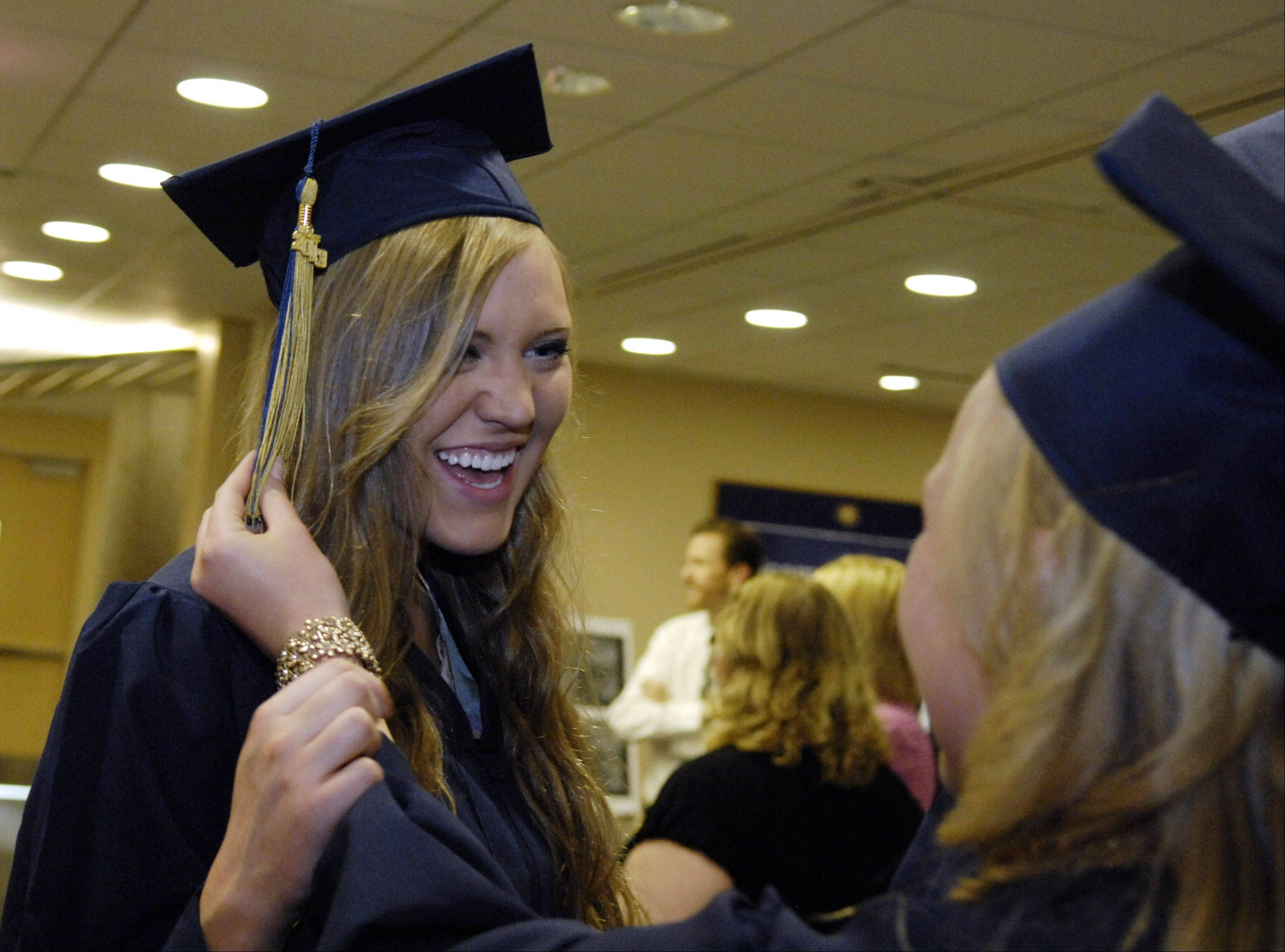 Kaya Abrahamson laughs as she gets a tassel adjustment before the Harvest Christian Academy commencement ceremony Saturday in Elgin.