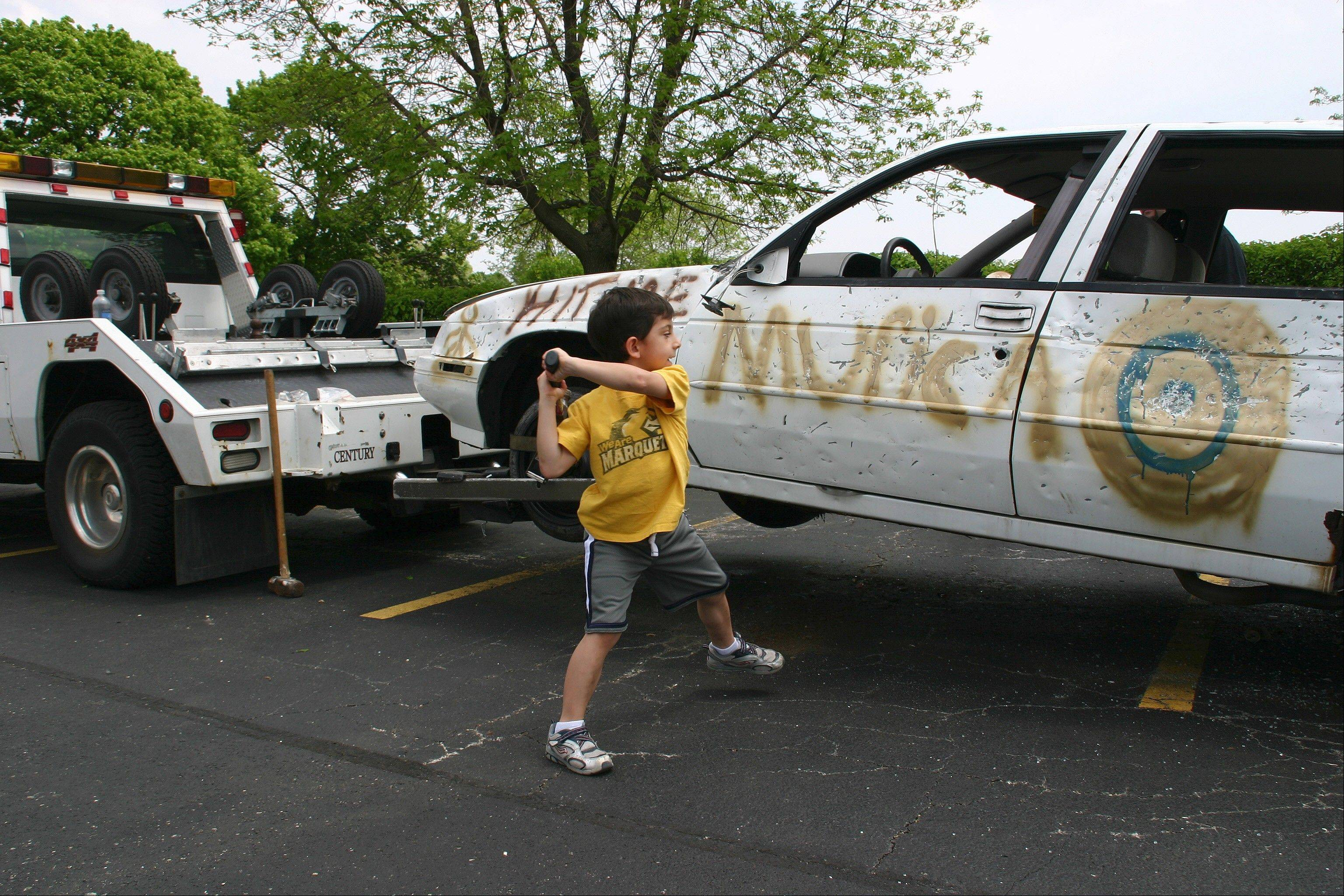 Aidan Graham winds up to give the Accurate Auto wreck a pounding at the Touch a Truck event during Saturday's Spring Fun Fair in Des Plaines.