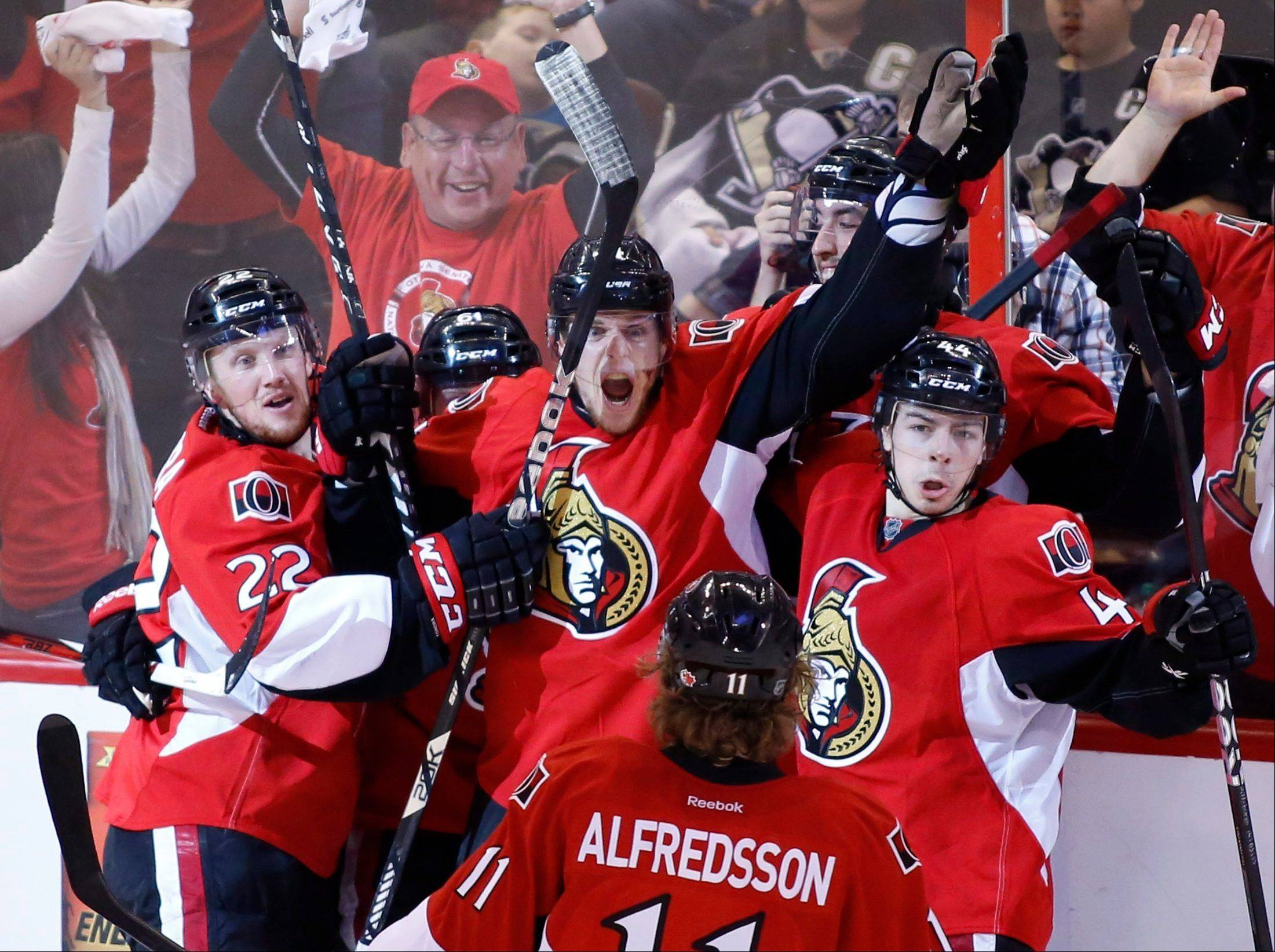Ottawa Senators' Erik Condra, left, Colin Greening, center, Jean-Gabriel Pageau, right, and Daniel Alfredsson celebrate after Greening scores the winning goal against the Pittsburgh Penguins during the second overtime period of Game 4 of their Stanley Cup Eastern Conference semi-final NHL hockey series at Scotiabank Place in Ottawa on Sunday, May 19, 2013.