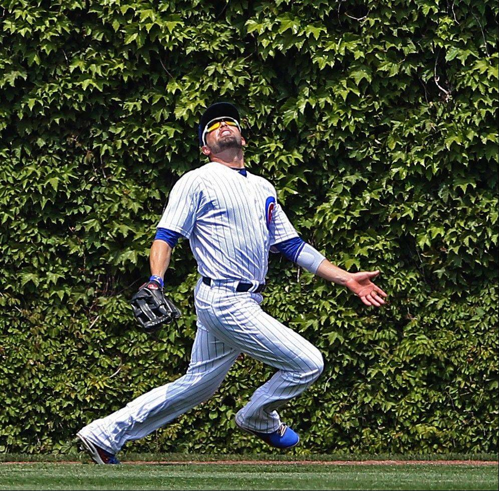 Cubs center fielder David DeJesus tries to locate a flyball hit by the Mets' Anthony Recker in the second inning Sunday at Wrigley Field. DeJesus managed to make the catch.
