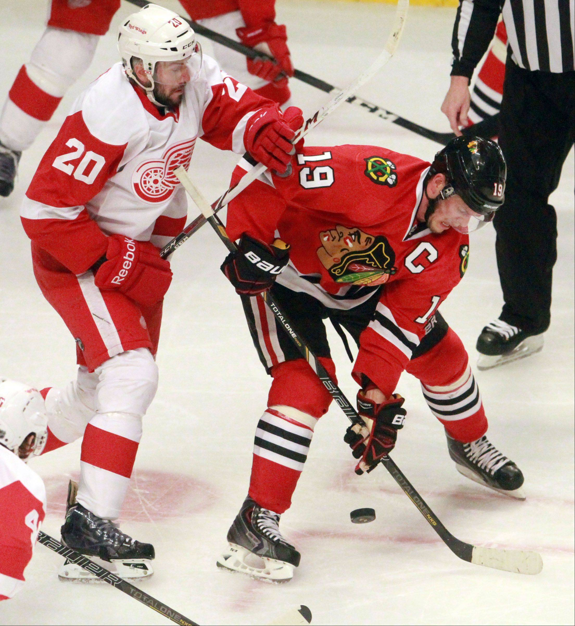 Blackhawks center Jonathan Toews looks to pass against the Red Wings' Drew Miller during the second period in Game 2 of the Western Conference semifinals at the United Center on Saturday. The Red Wings won 4-1 to tie the series at 1-1.