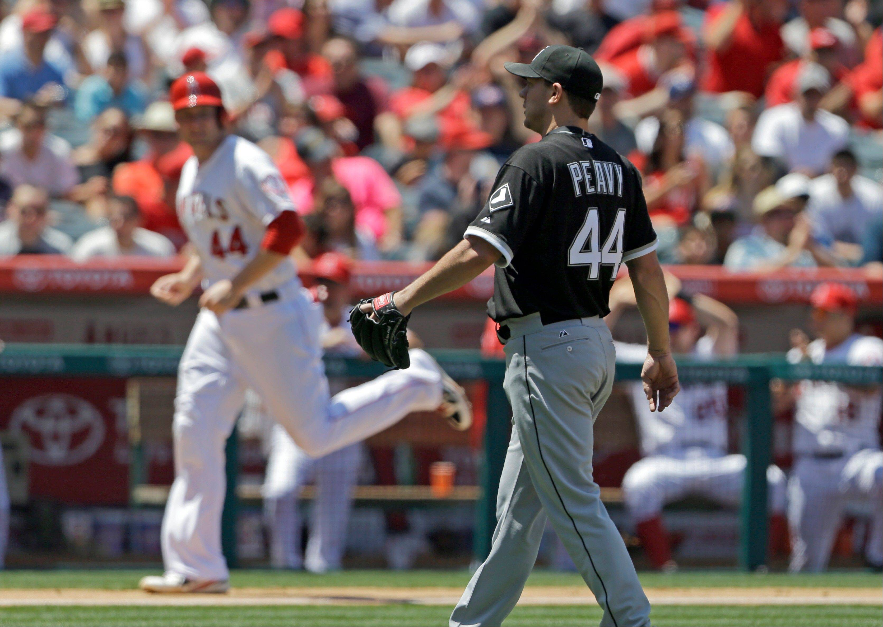 White Sox pitcher Jake Peavy watches as Los Angeles Angels' Mark Trumbo, background, scores on a bases-loaded walk in the fourth inning of a baseball game in Anaheim, Calif., Sunday, May 19, 2013.
