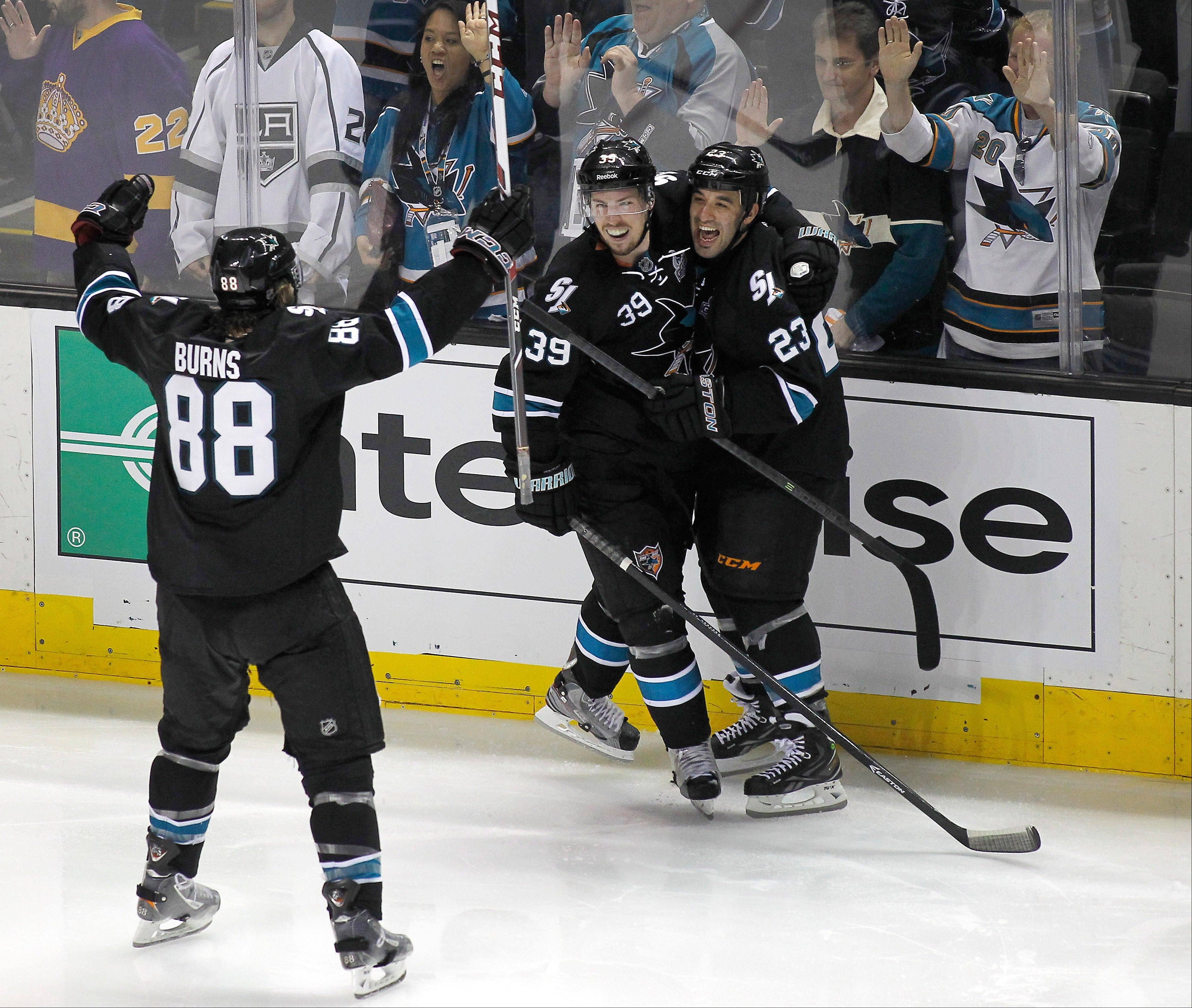 San Jose Sharks center Logan Couture (39) celebrates with Scott Gomez (23) and Brent Burns (88) after Couture scored the winning goal during overtime in Game 3 of their second-round NHL hockey Stanley Cup playoff series, Saturday, May 18, 2013, in San Jose, Calif. San Jose won in overtime 2-1.