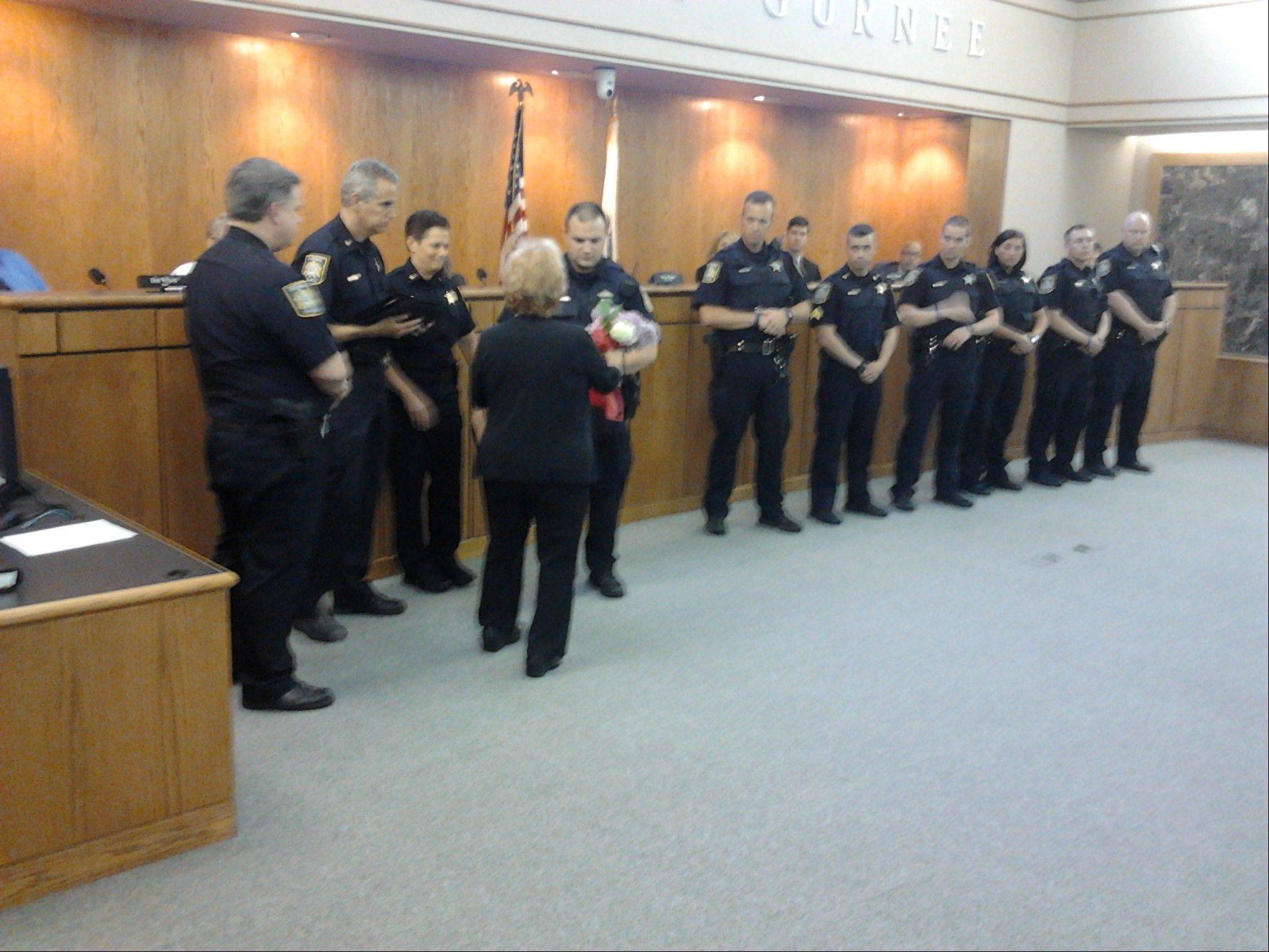 Alliance Against Intoxicated Motorists court watch director Cathy Stanley presents flowers to Gurnee police officer J.R. Nauseda at a ceremony Monday night. Nauseda made the most DUI arrests in Gurnee in 2012.