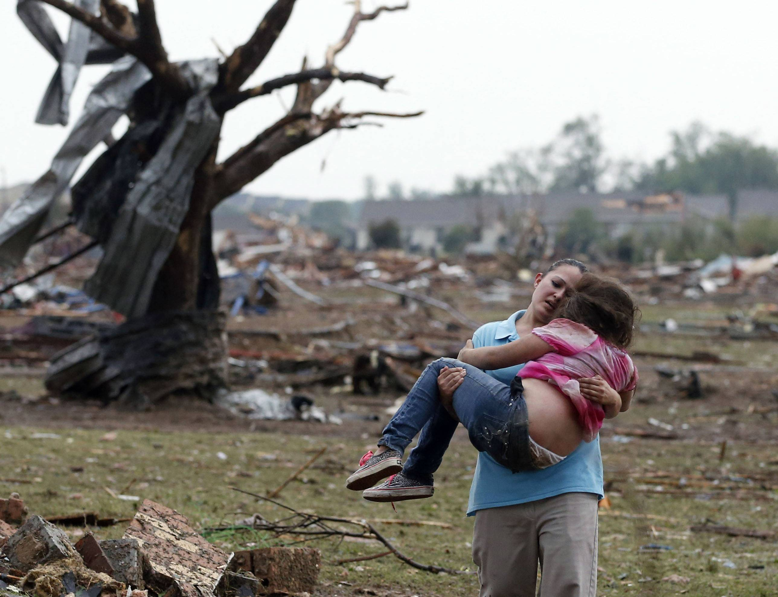 A woman carries a child through a field near the collapsed Plaza Towers Elementary School in Moore, Okla., Monday, May 20, 2013. The relationship between the woman and the child was not immediately known. A tornado as much as half a mile (.8 kilometers) wide with winds up to 200 mph (320 kph) roared through the Oklahoma City suburbs Monday