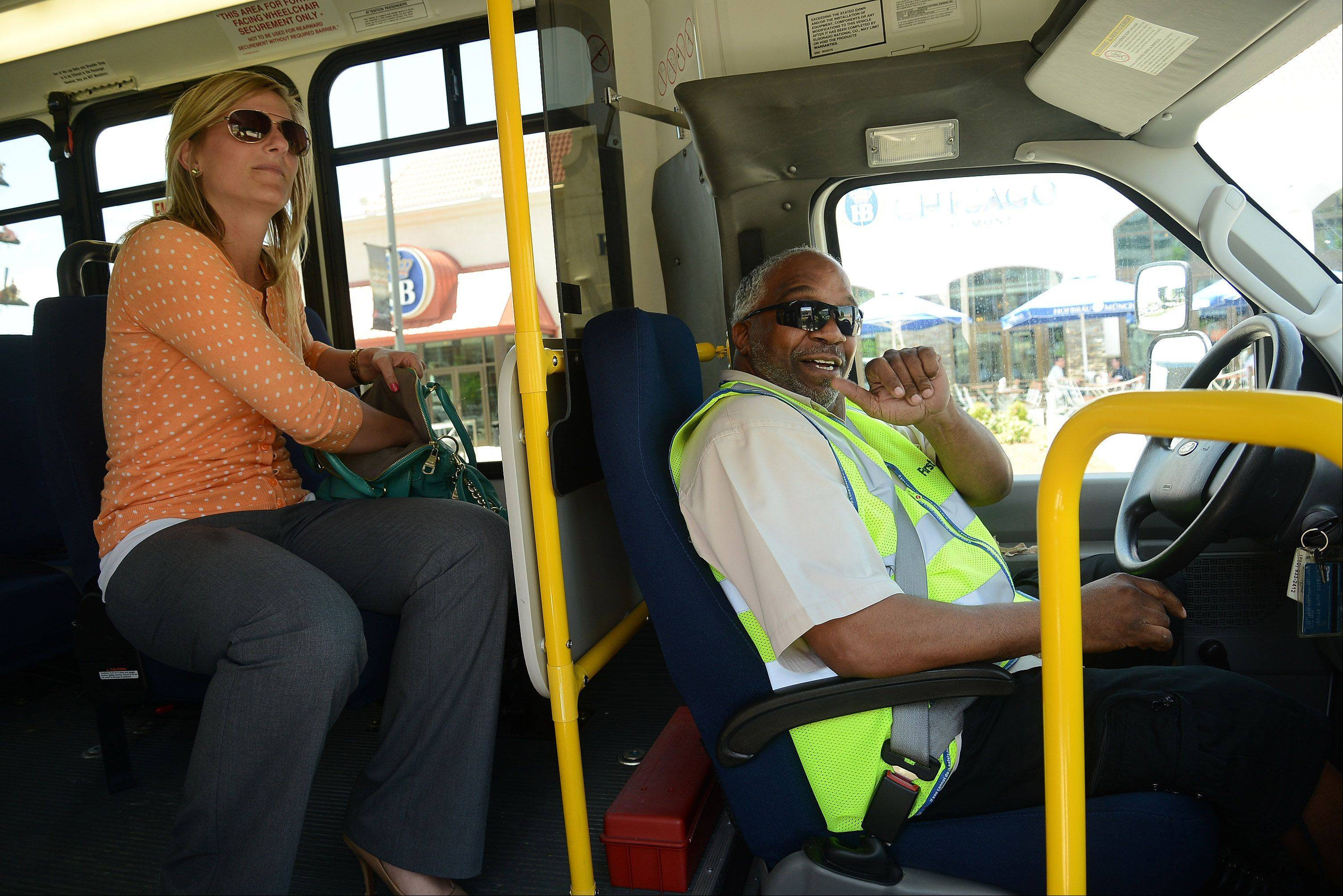 Senior Planner for Pace Charlotte O'Donnell checks with driver Michael Holmes on one of two Rosemont Lunchtime Circulator's making its rounds through the MB Financial Park at Rosemont entertainment district. The free service launched Monday.