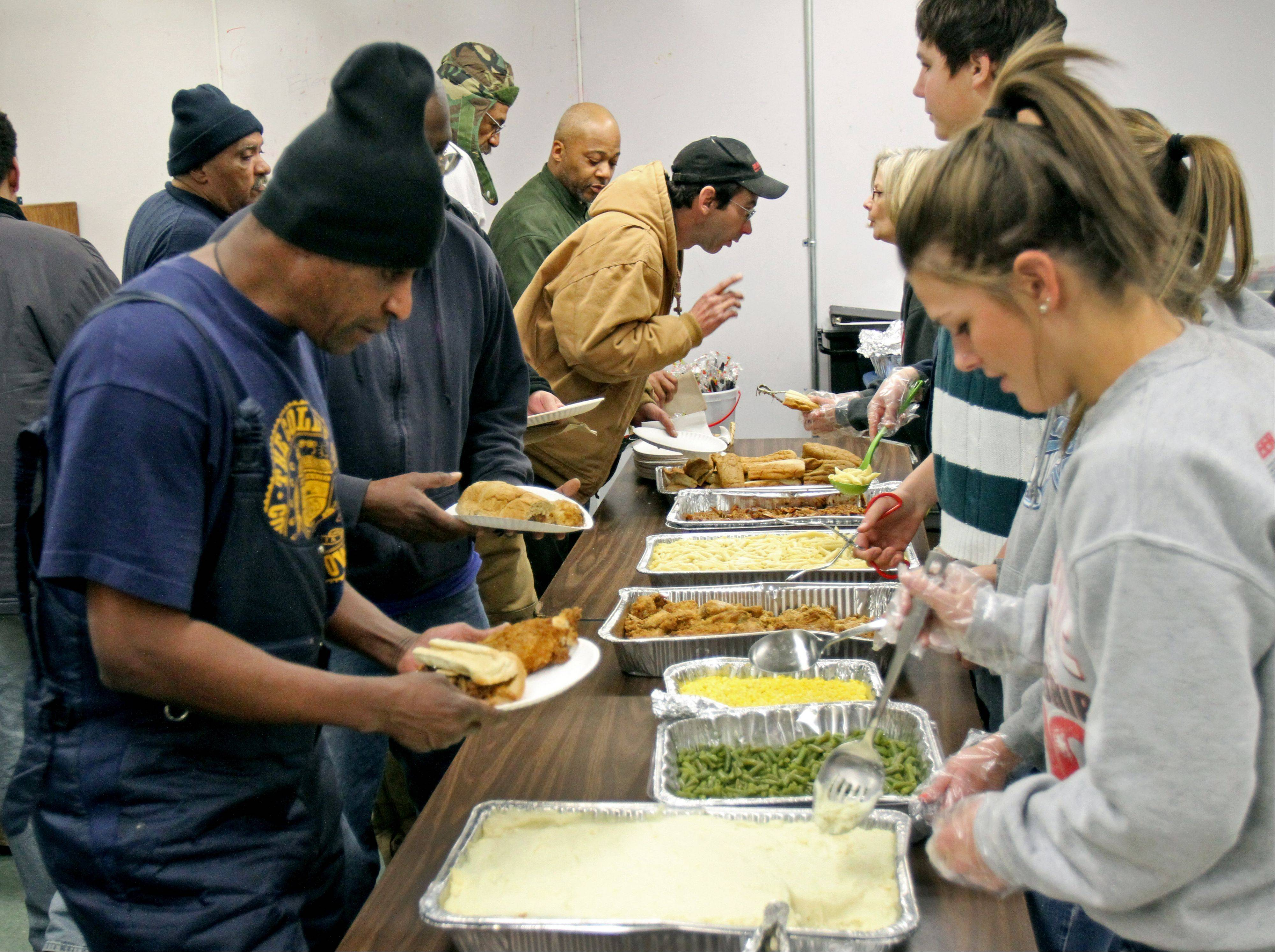 Steve Lundy/DAILY HERALD PADS guests line up for a meal as volunteers dish out some food at the Libertyville PADS shelter sponsored by St. Joseph Catholic Church in this file photo from 2010. More poor people live in the nation's suburbs than in urban cities because of affordable housing, service-sector jobs and the increased use of housing vouchers, according to a study released Monday.