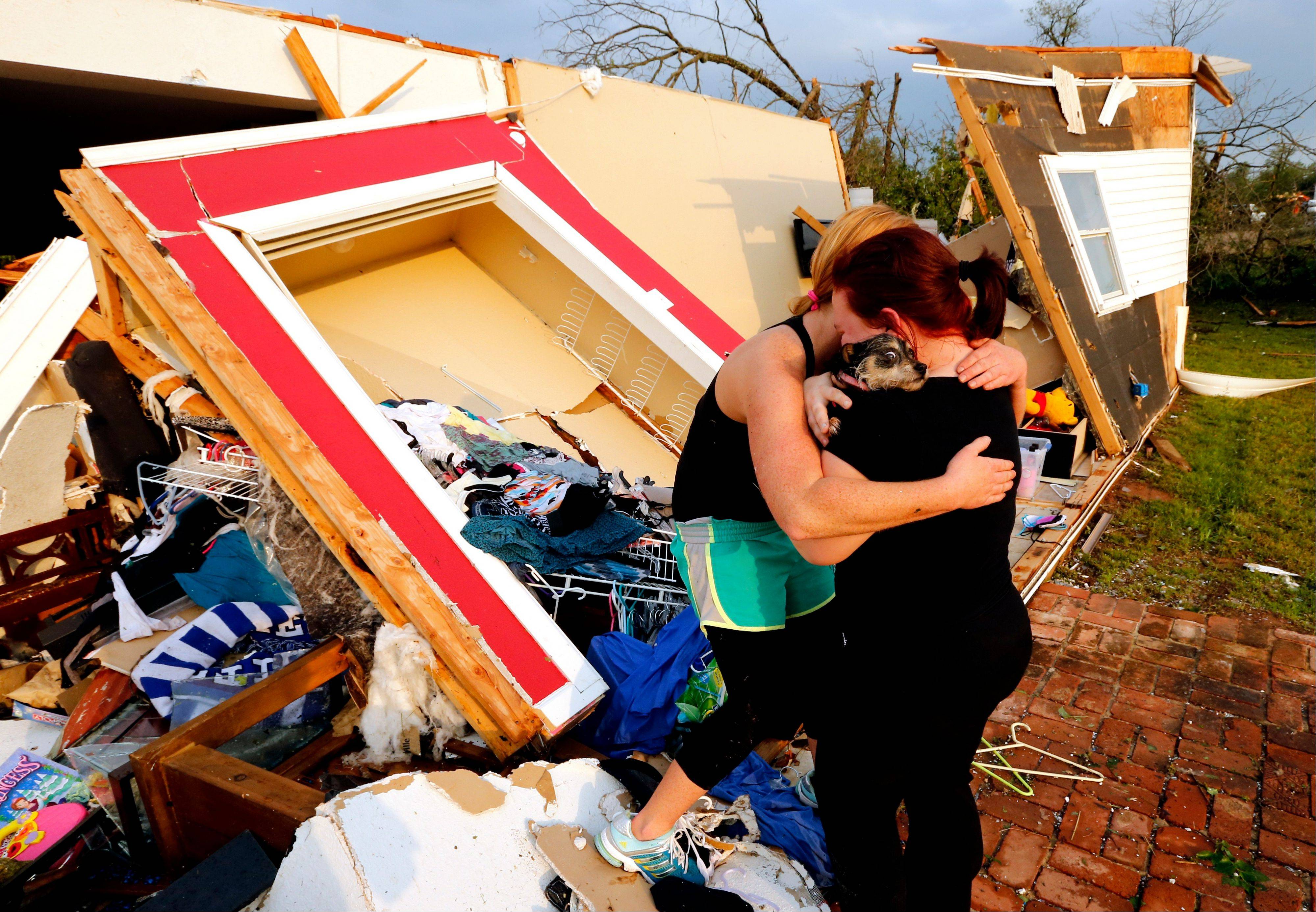 Alli Christian, left, returns Jessica Wilkinson's dog Bella to her after finding the pet amid the wreckage of Wilkinson's home shortly after a tornado struck near 156th street and Franklin Road on Sunday, May 19, 2013, in Norman, Okla. No one was in the home when the storm struck.