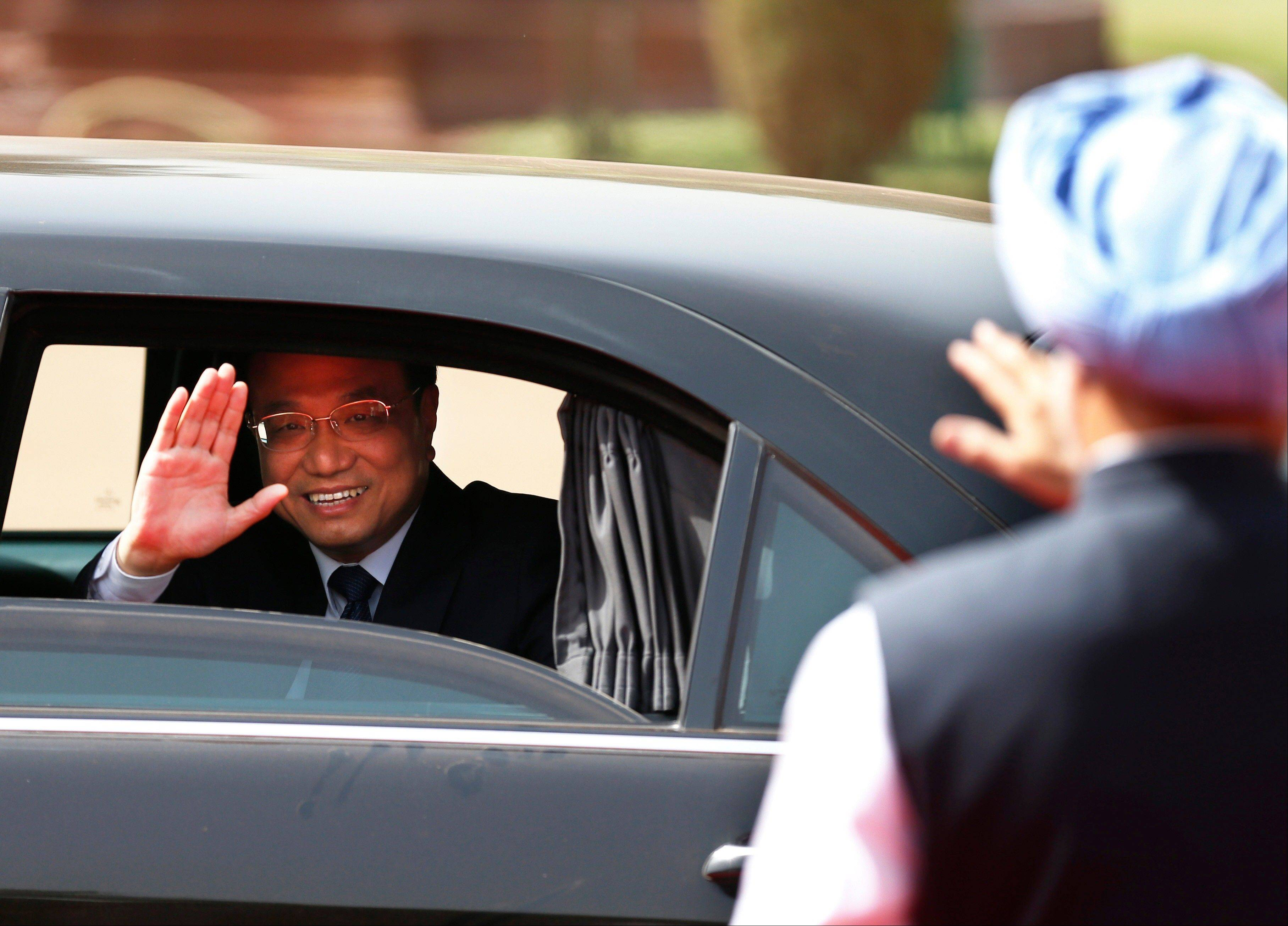 Chinese Premier Li Keqiang waves to Indian Prime Minister Manmohan Singh, right, as he leaves the Indian Presidential Palace after his ceremonial reception in New Delhi, India, Monday. Just weeks after a tense border standoff, Li visited India on his first foreign three-day trip as the neighboring giants look to speed up efforts to settle a decades-old boundary dispute and boost economic ties.