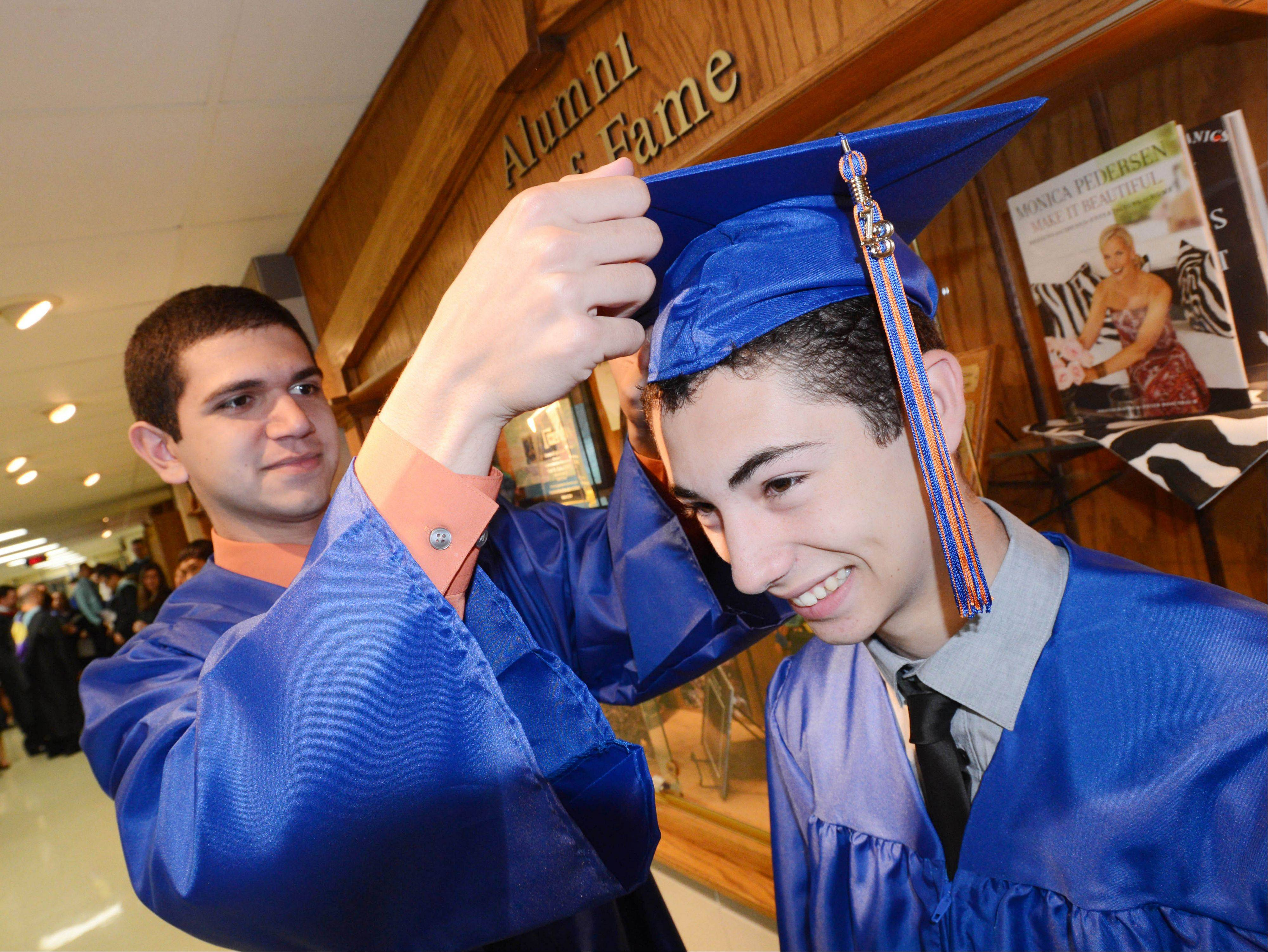 Simon Jiries helps Marco Bartolomeo with his hat during the Class of 2013 Commencement at Fenton High School Sunday. To see more photos and order reprints, visit www.dailyherald.com/galleries/news/graduations/