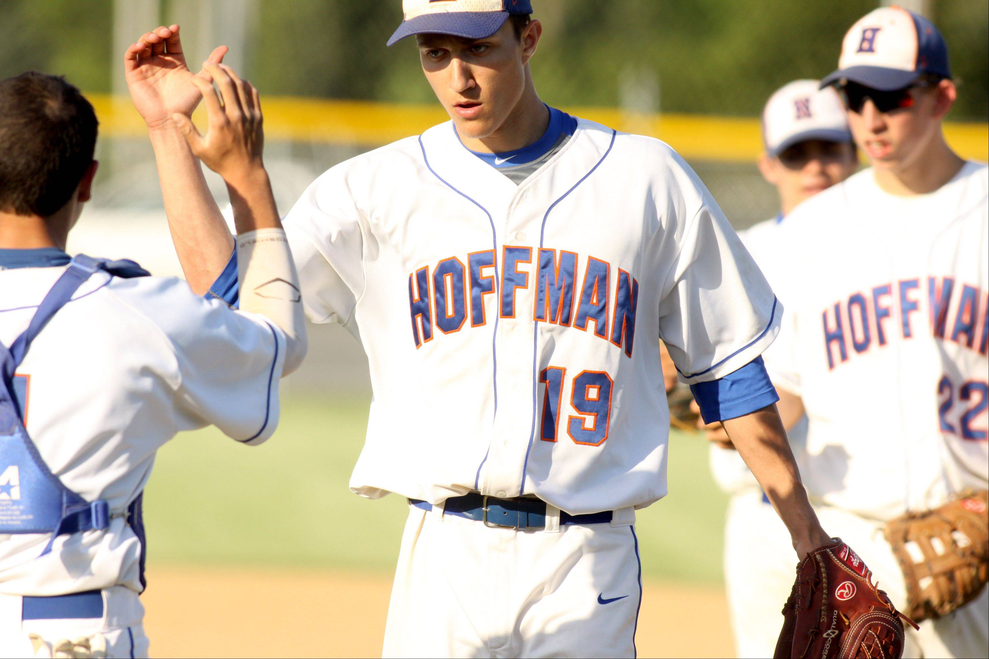 Hoffman Estates pitcher Jimmy Ward, center, high-fives his battery mate Brandon Weidner after the Hawks won 3-1 in regional action at Elgin on Monday.
