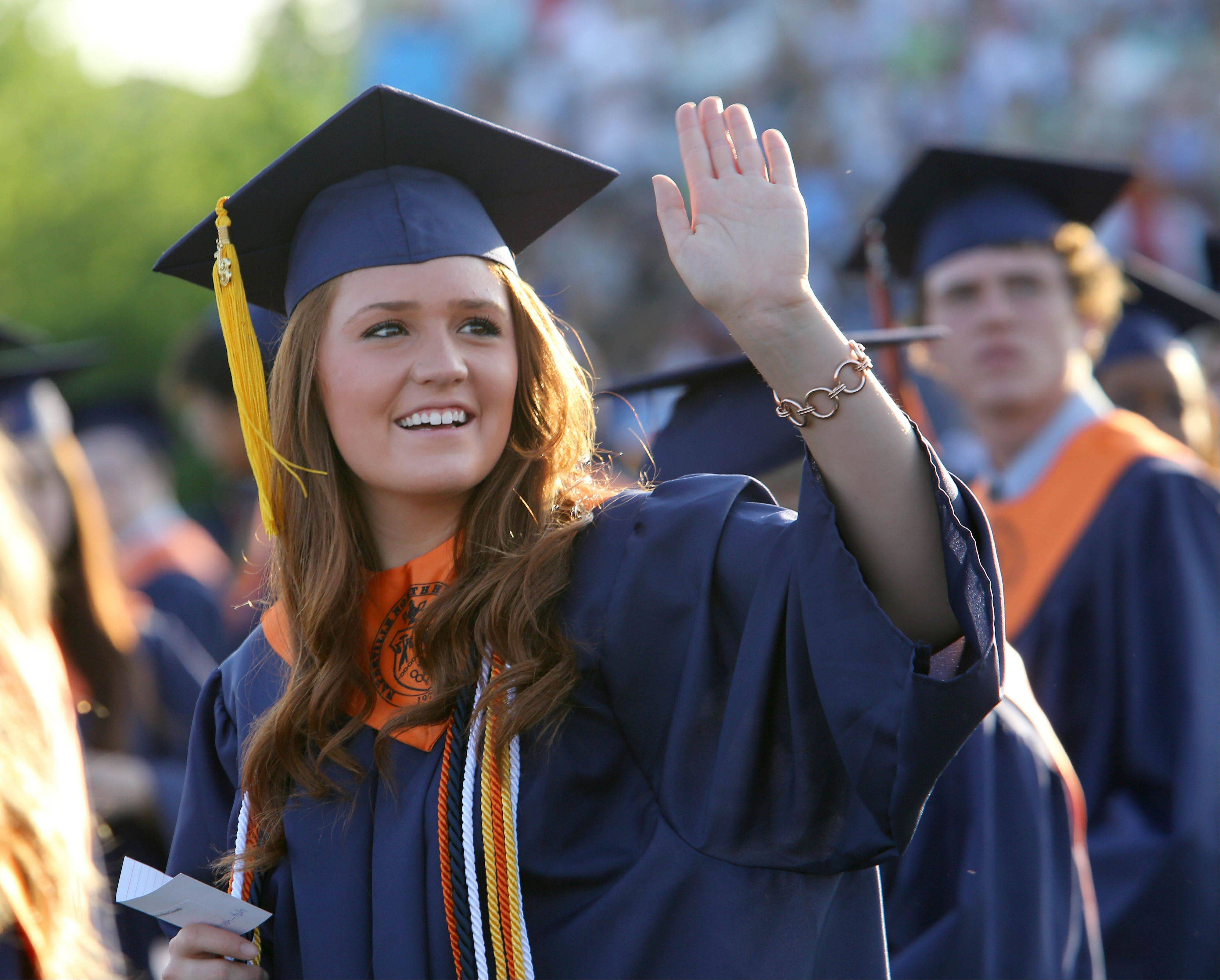 Rebecca Cravatta gives a wave during the Naperville North graduation ceremony on Monday.