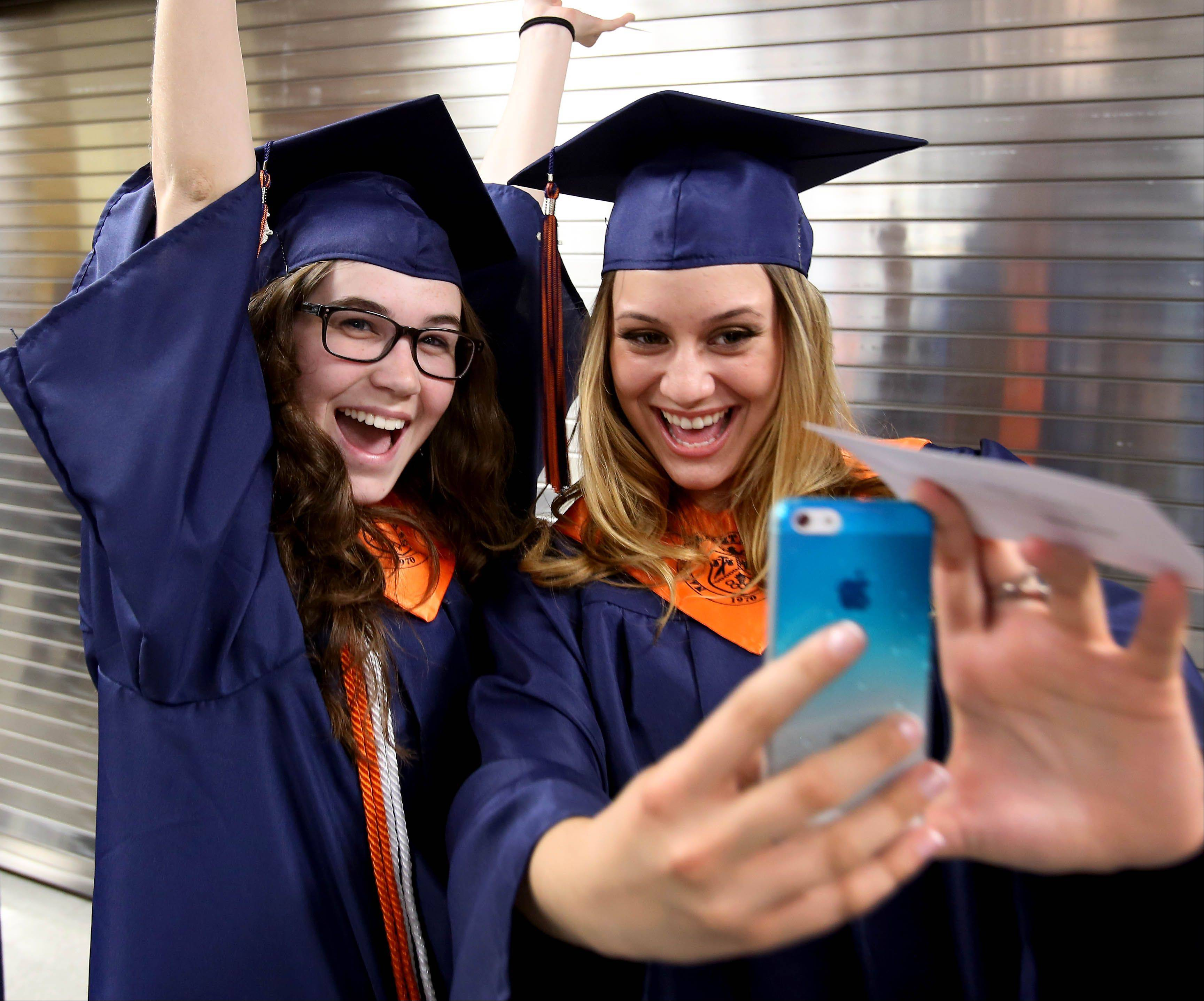 Chloe Gasser, left and Ivana Garotic, right, get a cell phone photo before the Naperville North graduation on Monday.