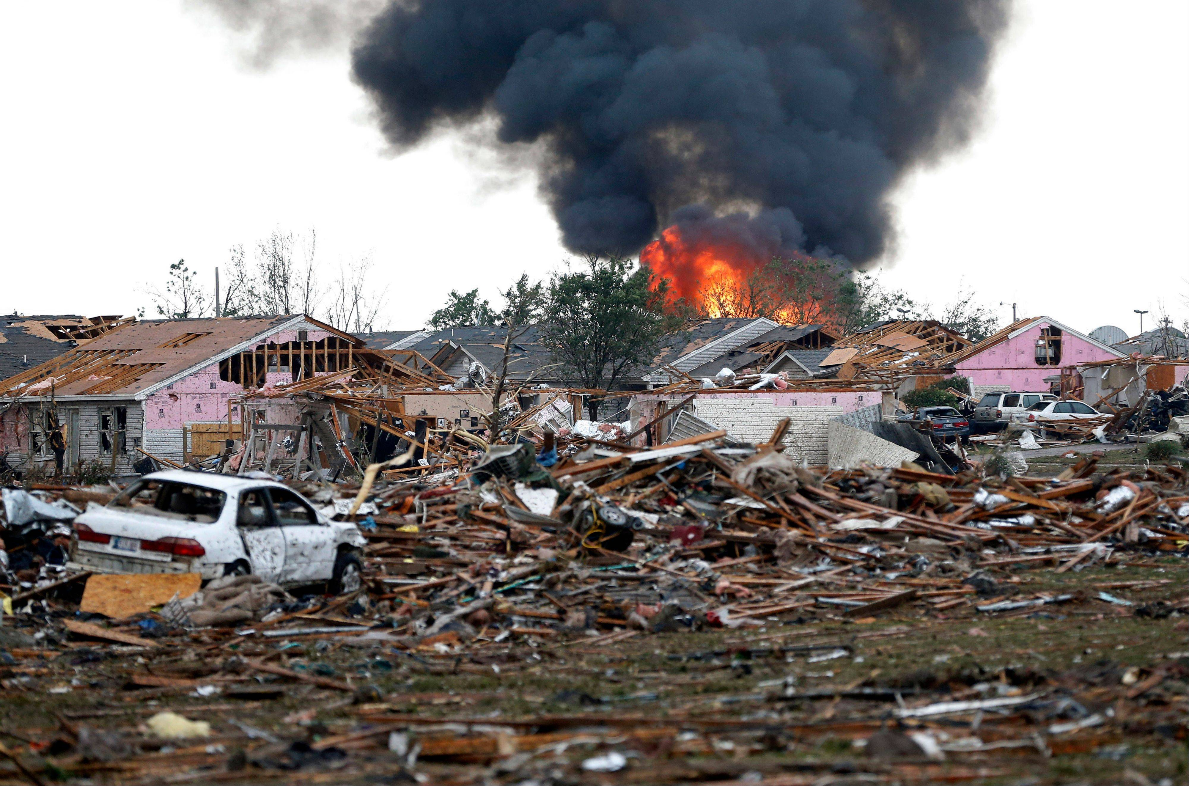 A fire burns in the Tower Plaza Addition in Moore, Okla., following a tornado Monday, May 20, 2013. A tornado as much as a mile wide with winds up to 200 mph roared through the Oklahoma City suburbs Monday, flattening entire neighborhoods, setting buildings on fire and landing a direct blow on an elementary school.