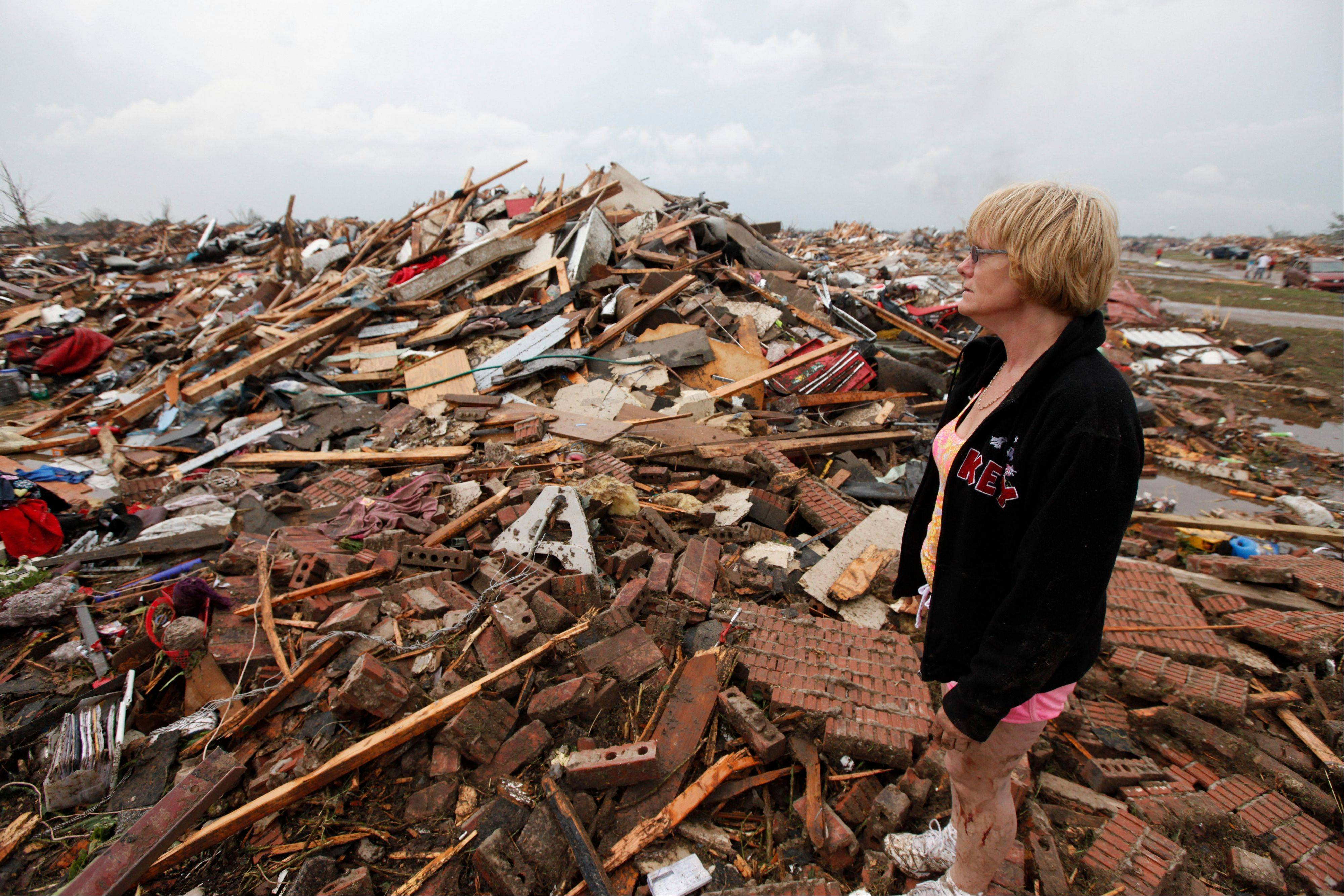 Resident Kim Schwab looks over her destroyed home in south Oklahoma City, Monday, May 20, 2013. A monstrous tornado roared through the Oklahoma City suburbs, flattening entire neighborhoods with winds up to 200 mph, setting buildings on fire and landing a direct blow on an elementary school.