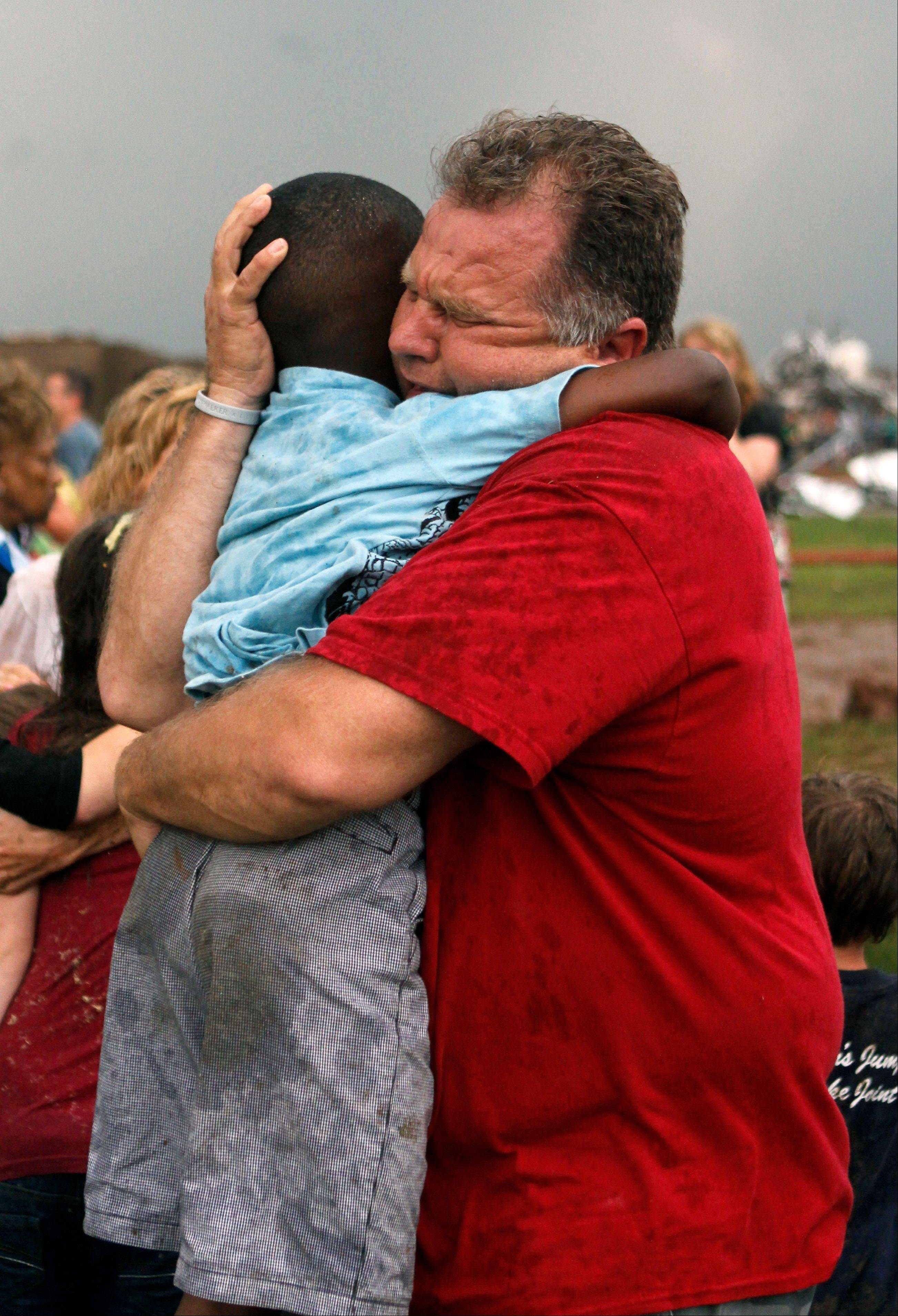 A teacher hugs a child at Briarwood Elementary school after a tornado destroyed the school in south Oklahoma City, Monday, May 20, 2013. A monstrous tornado roared through the Oklahoma City suburbs, flattening entire neighborhoods with winds up to 200 mph, setting buildings on fire and landing a direct blow on an elementary school.
