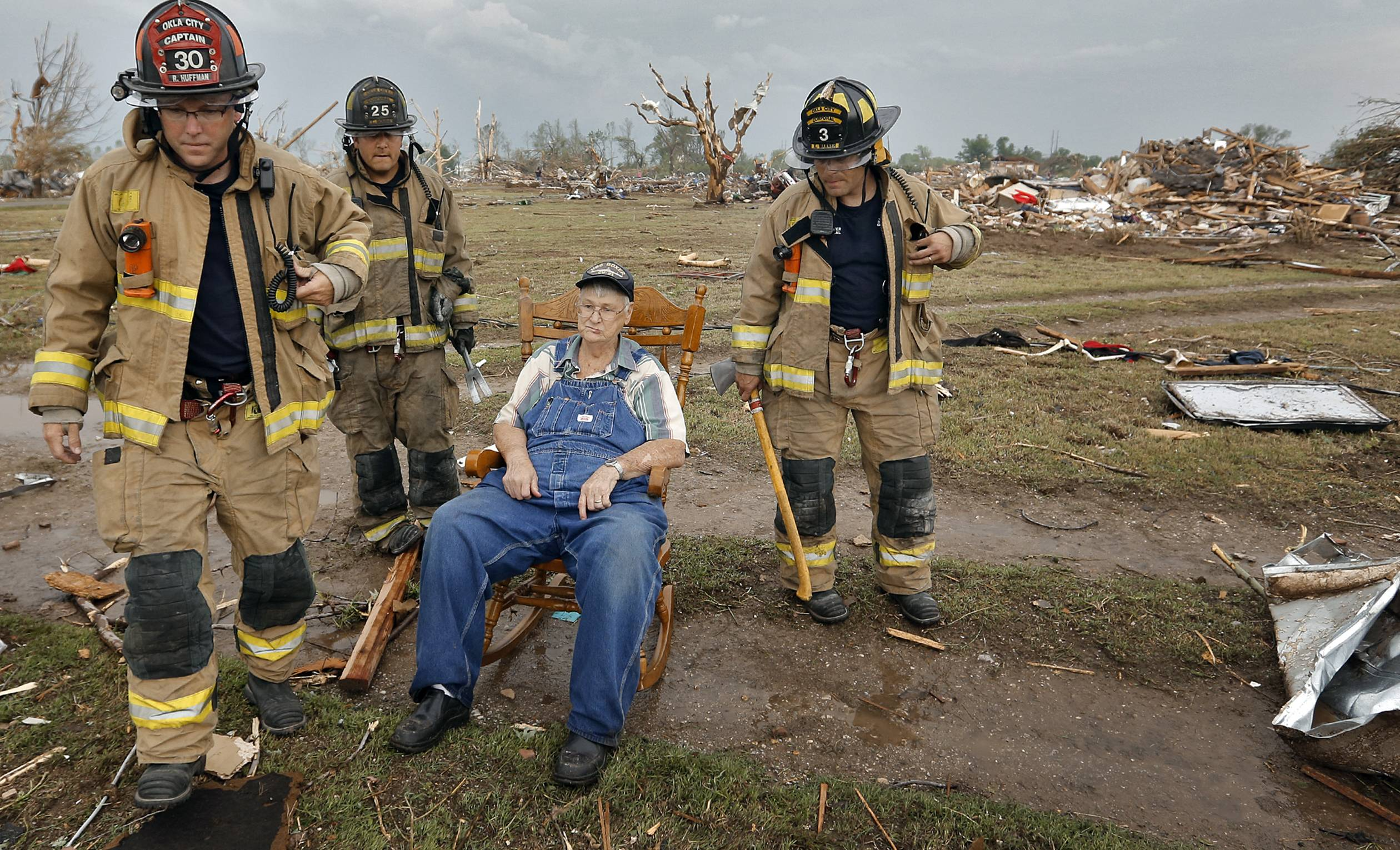 Oklahoma City firefighters check on the status of Gene Tripp as he sits in his rocking chair where his home once stood after being destroyed by a tornado that hit the area, Monday, May 20, 2013 in Oklahoma City, Okla.