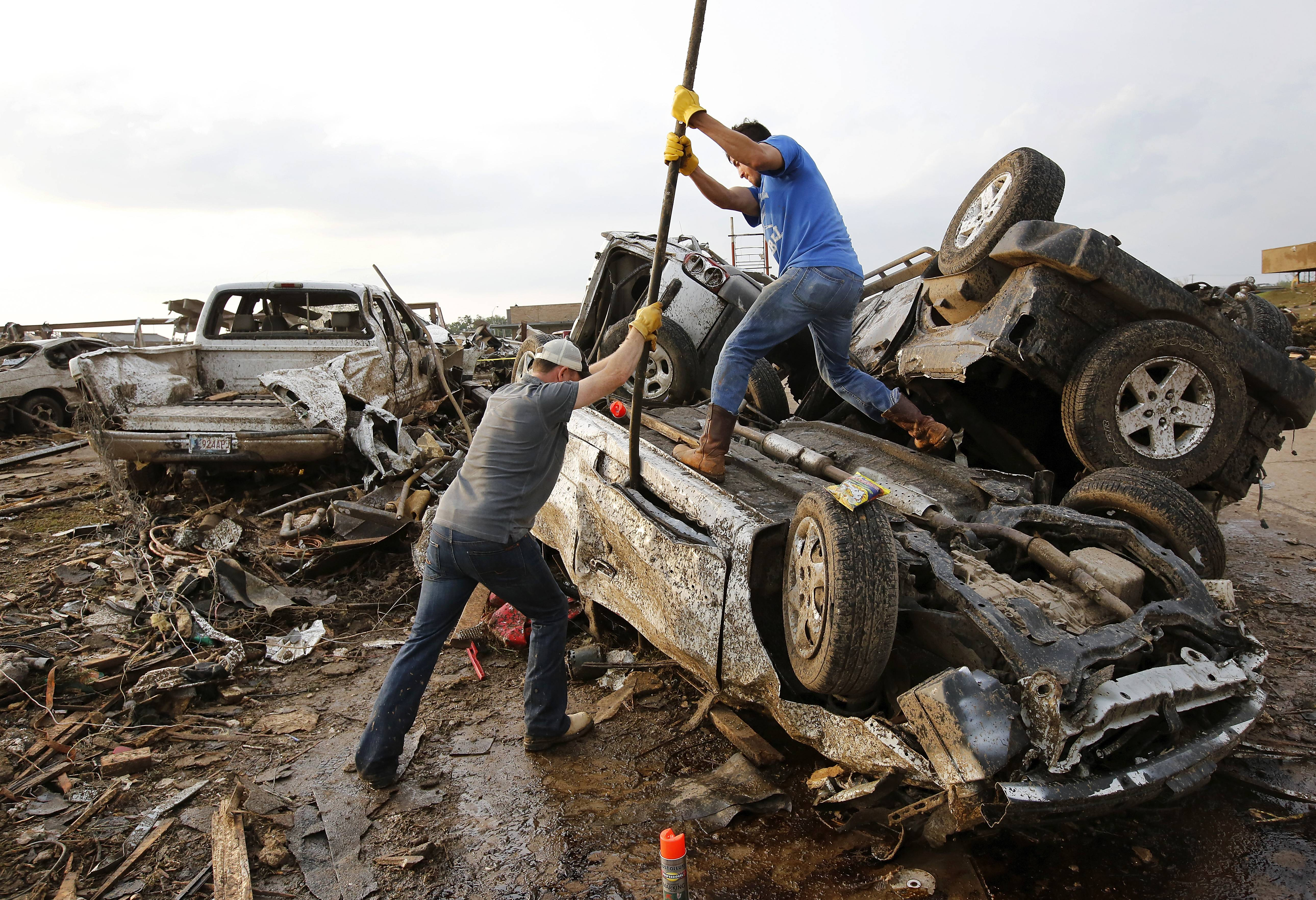 Two men attempt  to pry open a door on this car to check for victims in a business parking lot west of I-35 south of 4th Street  in Moore, on Monday, May 20, 2013.A monstrous tornado roared through the Oklahoma City suburbs, flattening entire neighborhoods with winds up to 200 mph, setting buildings on fire and landing a direct blow on an elementary school.