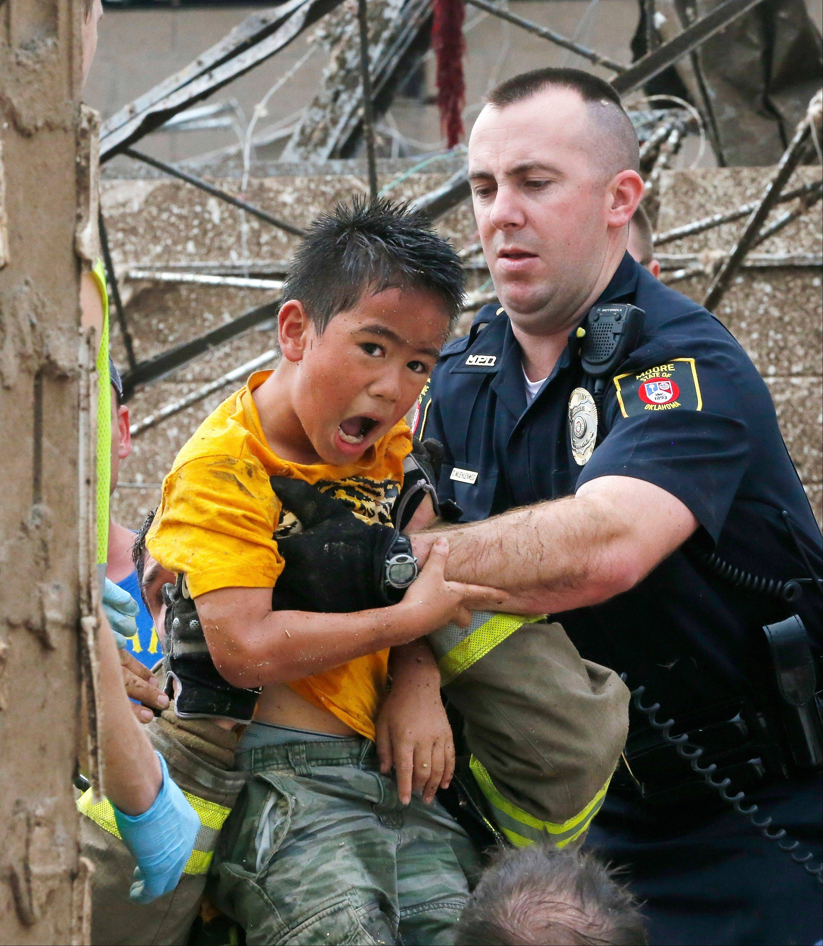 A boy is pulled from beneath a collapsed wall at the Plaza Towers Elementary School following a tornado in Moore, Okla., Monday, May 20, 2013. A tornado as much as a mile (1.6 kilometer) wide with winds up to 200 mph (320 kph) roared through the Oklahoma City suburbs Monday, flattening entire neighborhoods, setting buildings on fire and landing a direct blow on the elementary school.