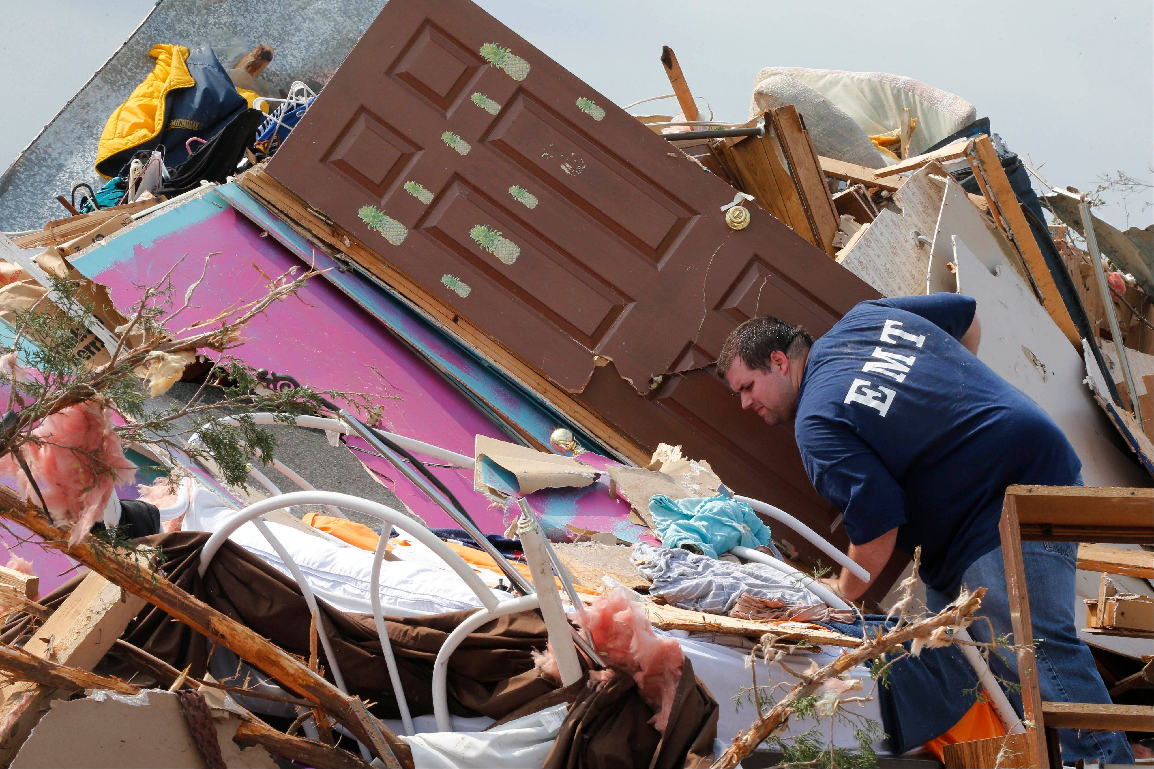 A resident who did not want to give his name, searches through the rubble of his mobile home in the Steelman Estates Mobile Home Park, destroyed by Sunday's tornado, near Shawnee, Okla., Monday, May 20, 2013. The tornado that slammed into Oklahoma on Sunday is now blamed for two deaths. Authorities say two men in their 70s have been found dead in or near a mobile home park outside of Shawnee.