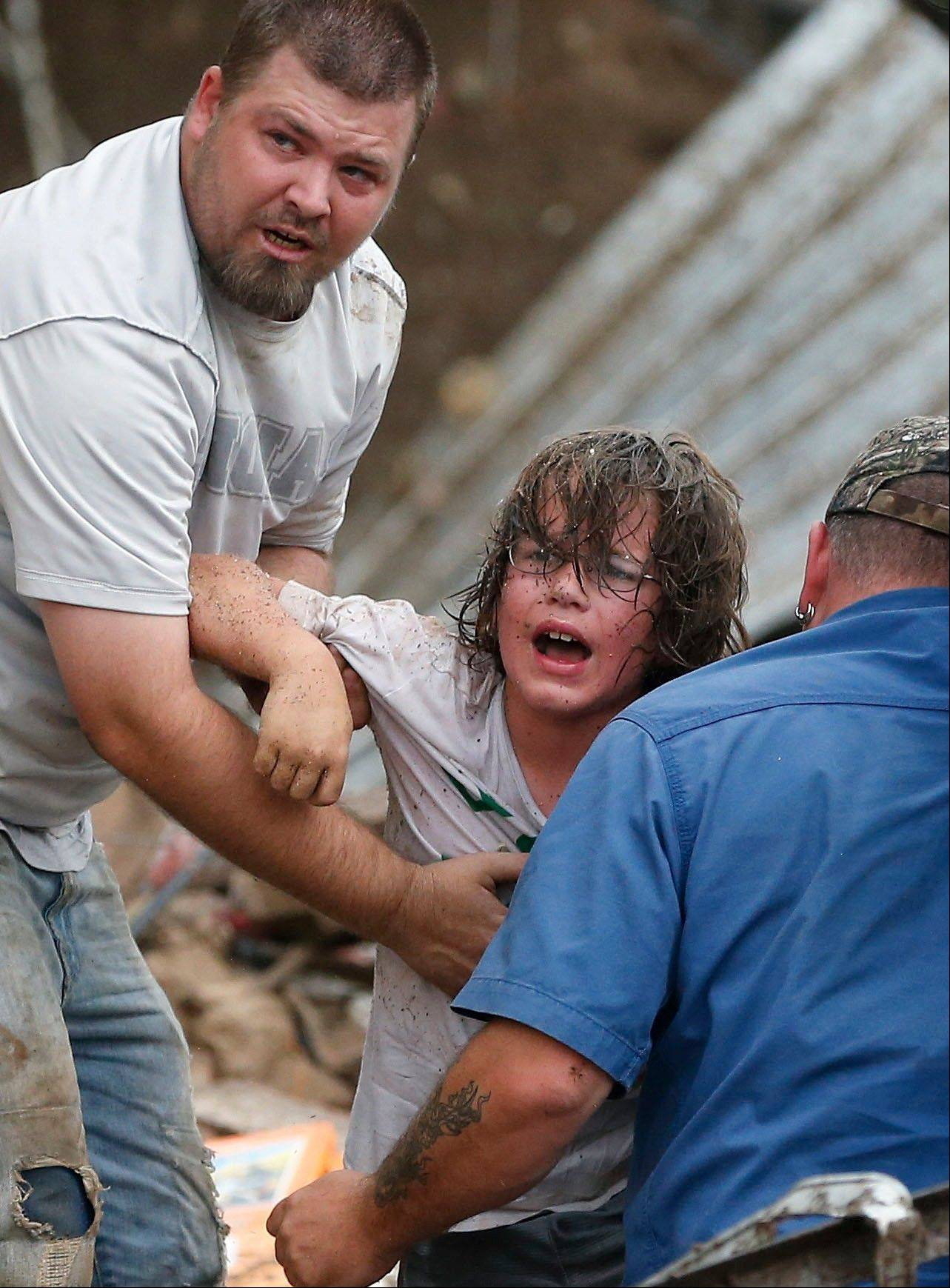 A child calls to his father after being pulled from the rubble of the Tower Plaza Elementary School following a tornado in Moore, Okla., Monday, May 20, 2013. A tornado as much as a mile (1.6 kilometers) wide with winds up to 200 mph (320 kph) roared through the Oklahoma City suburbs Monday, flattening entire neighborhoods, setting buildings on fire and landing a direct blow on the elementary school.
