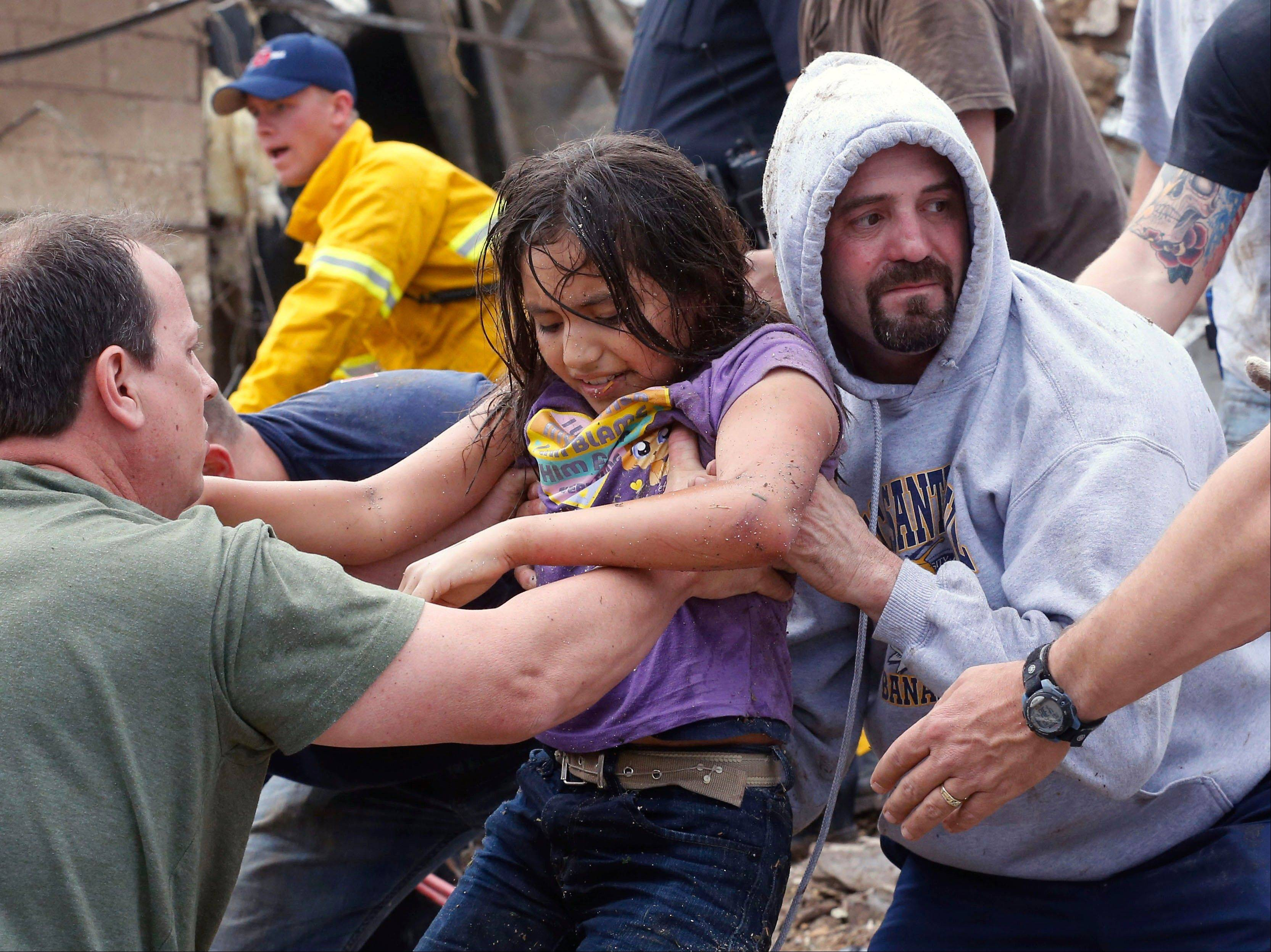 child is passed along a human chain of people after being pulled from the rubble of the Plaza Towers Elementary School in Moore, Okla., and passed along a human chain of rescuers Monday, May 20, 2013. A tornado as much as a mile (1.6 kilometers) wide with winds up to 200 mph (320 kph) roared through the Oklahoma City suburbs Monday, flattening entire neighborhoods, setting buildings on fire and landing a direct blow on an elementary school.