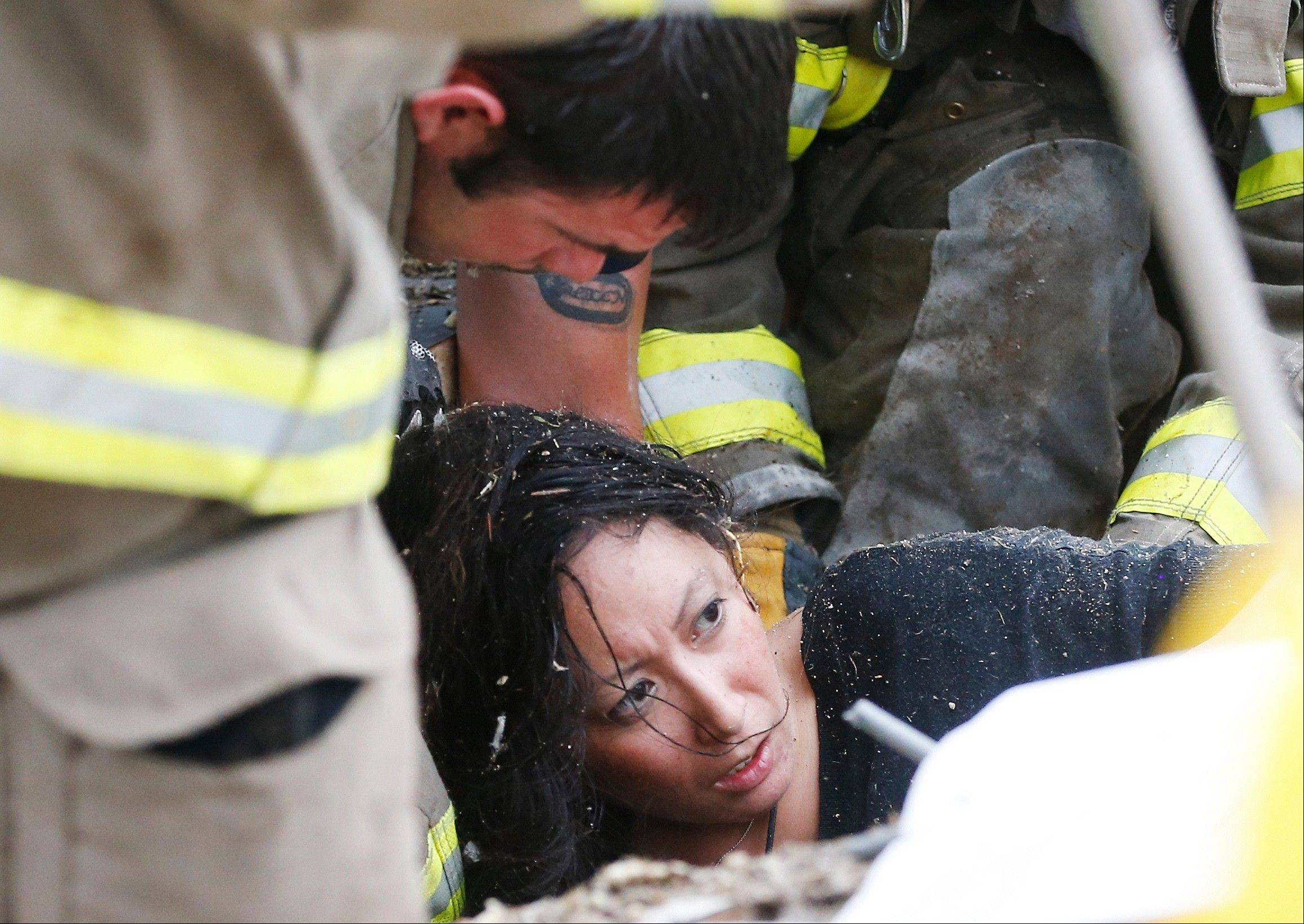 A woman is pulled out from under tornado debris at the Plaza Towers School in Moore, Okla., Monday, May 20, 2013. A tornado as much as a mile (1.6 kilometers) wide with winds up to 200 mph (320 kph) roared through the Oklahoma City suburbs Monday, flattening entire neighborhoods, setting buildings on fire and landing a direct blow on an elementary school.