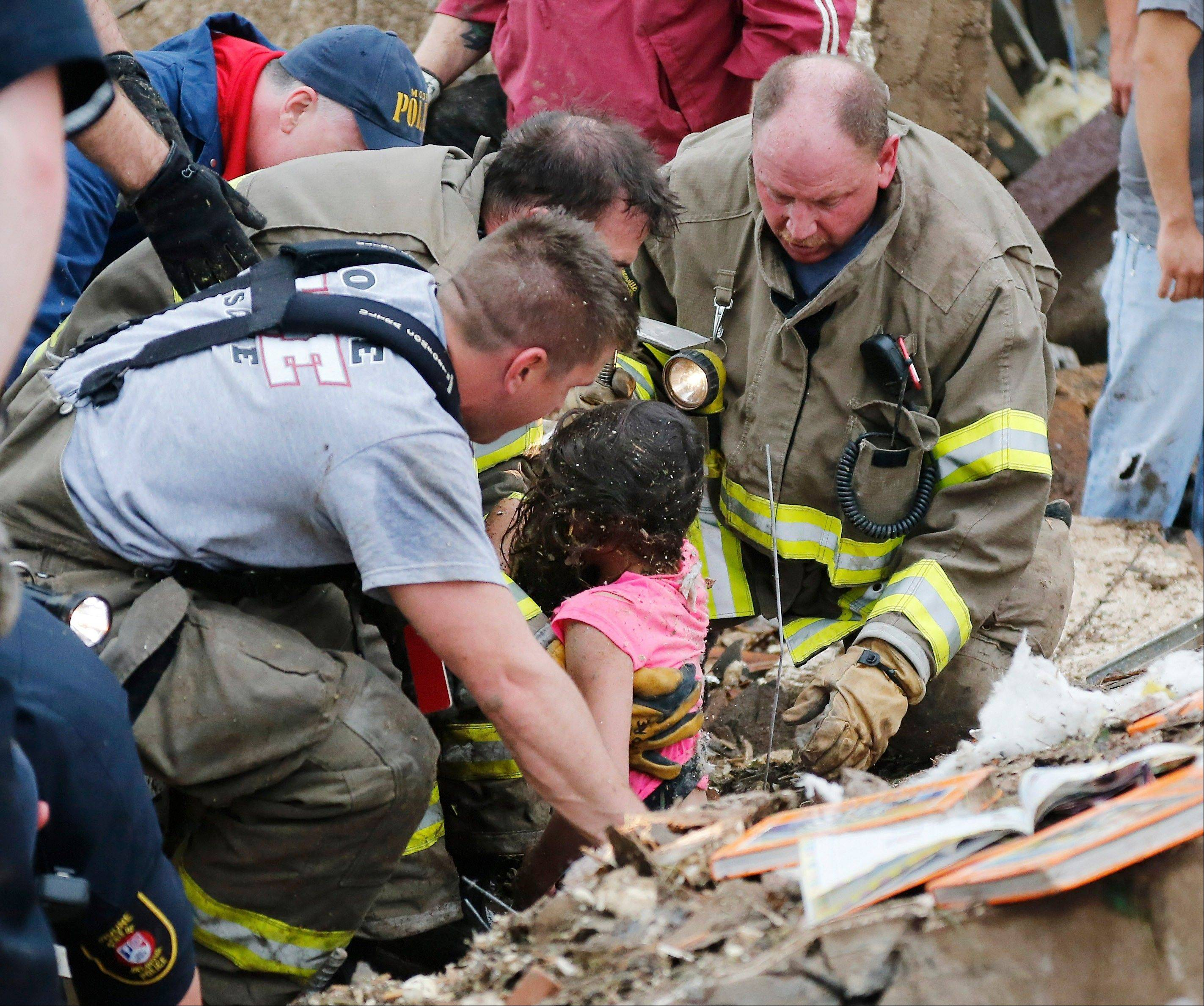 A child is pulled from beneath a collapsed wall at the Plaza Towers Elementary School in following a tornado in Moore, Okla., Monday.