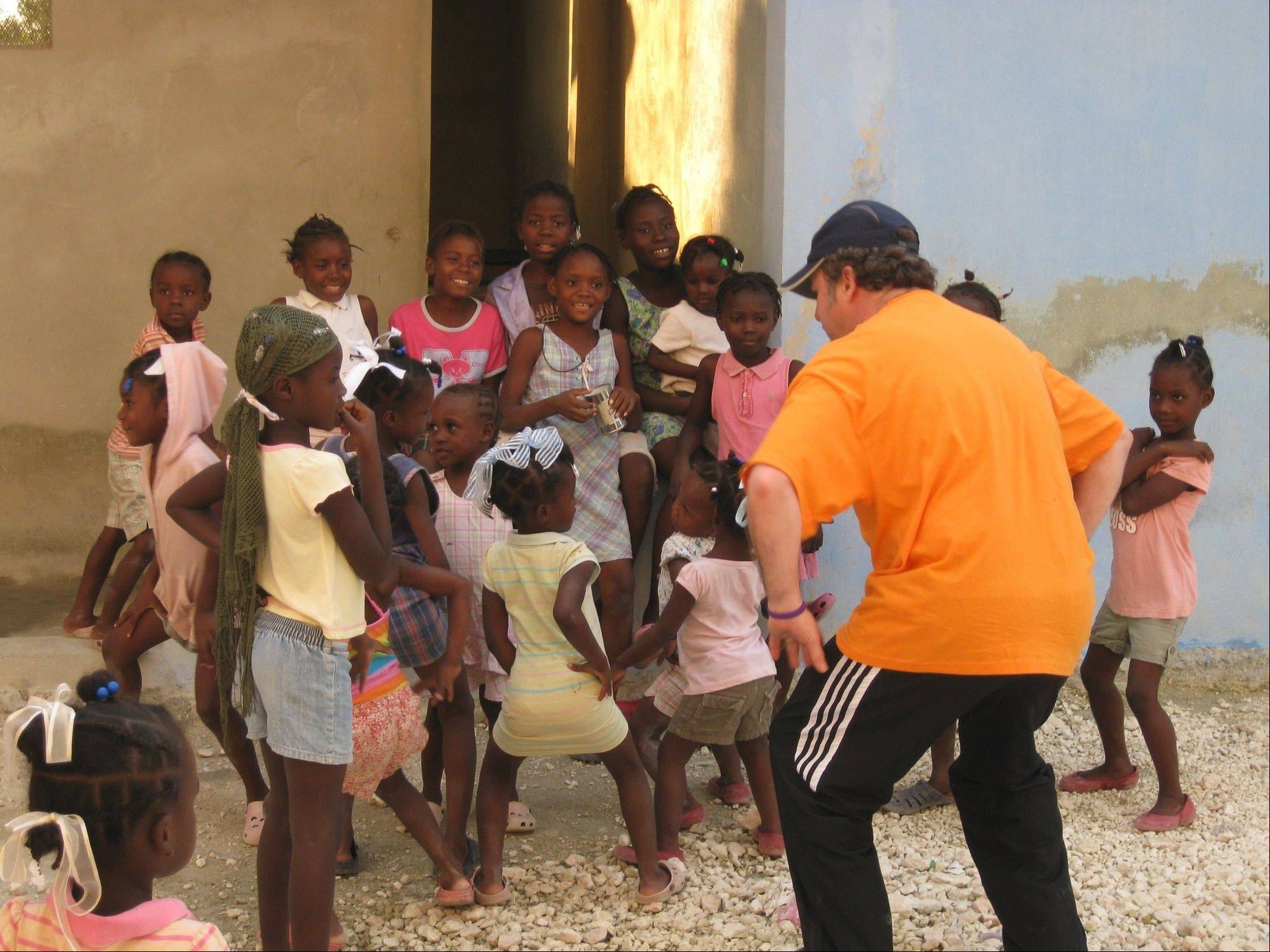 Brian Reynolds of Arlington Heights goofs around with schoolchildren in Haiti.