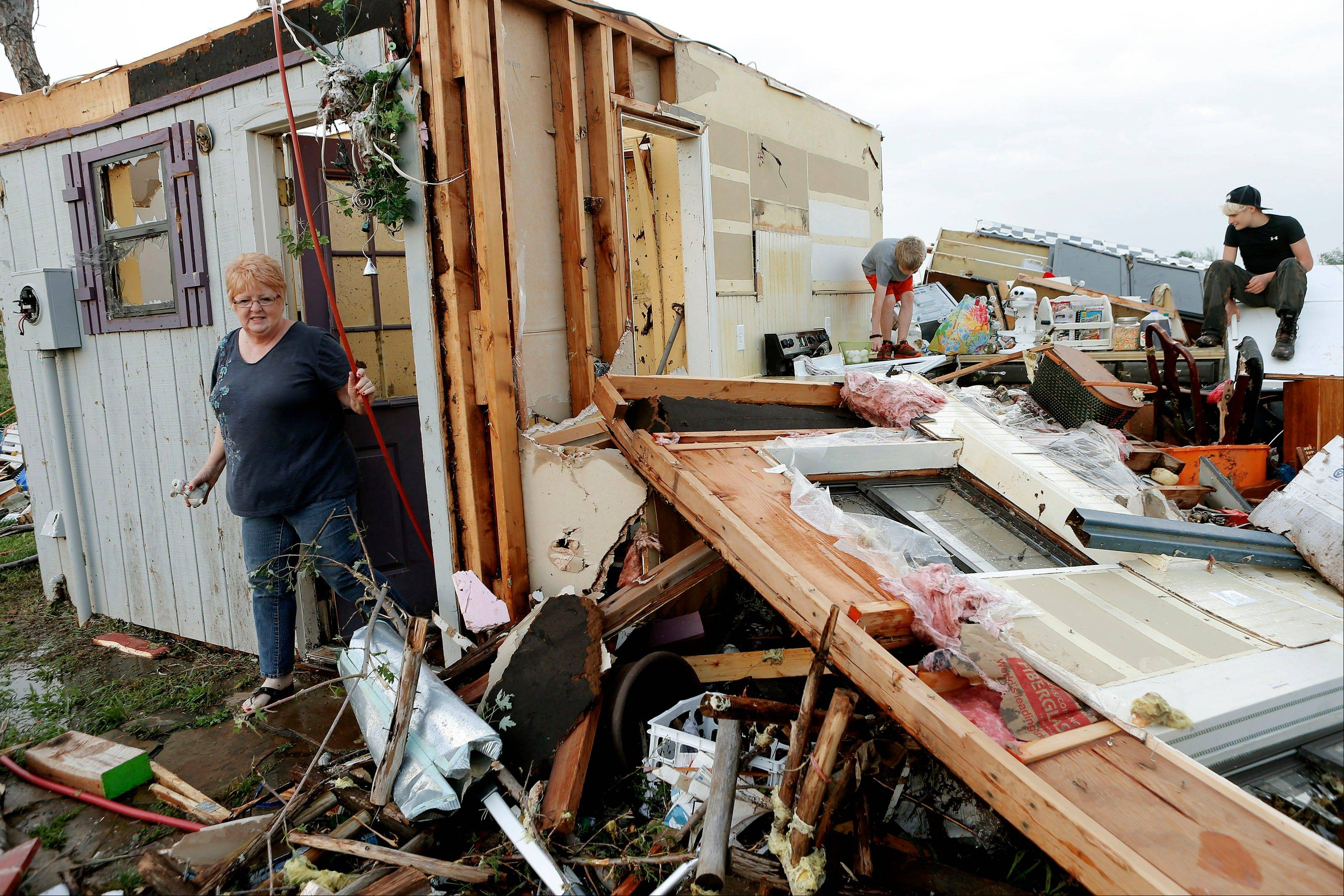 Marlena Hodson walks out of her home as her grandsons, Campbell Miller, 10, and Dillon Miller, 13, at right, help her sort through belongings after a tornado damaged her home Carney Okla., on Sunday, May 19, 2013. Hodson and her family left the home to escape the tornado.