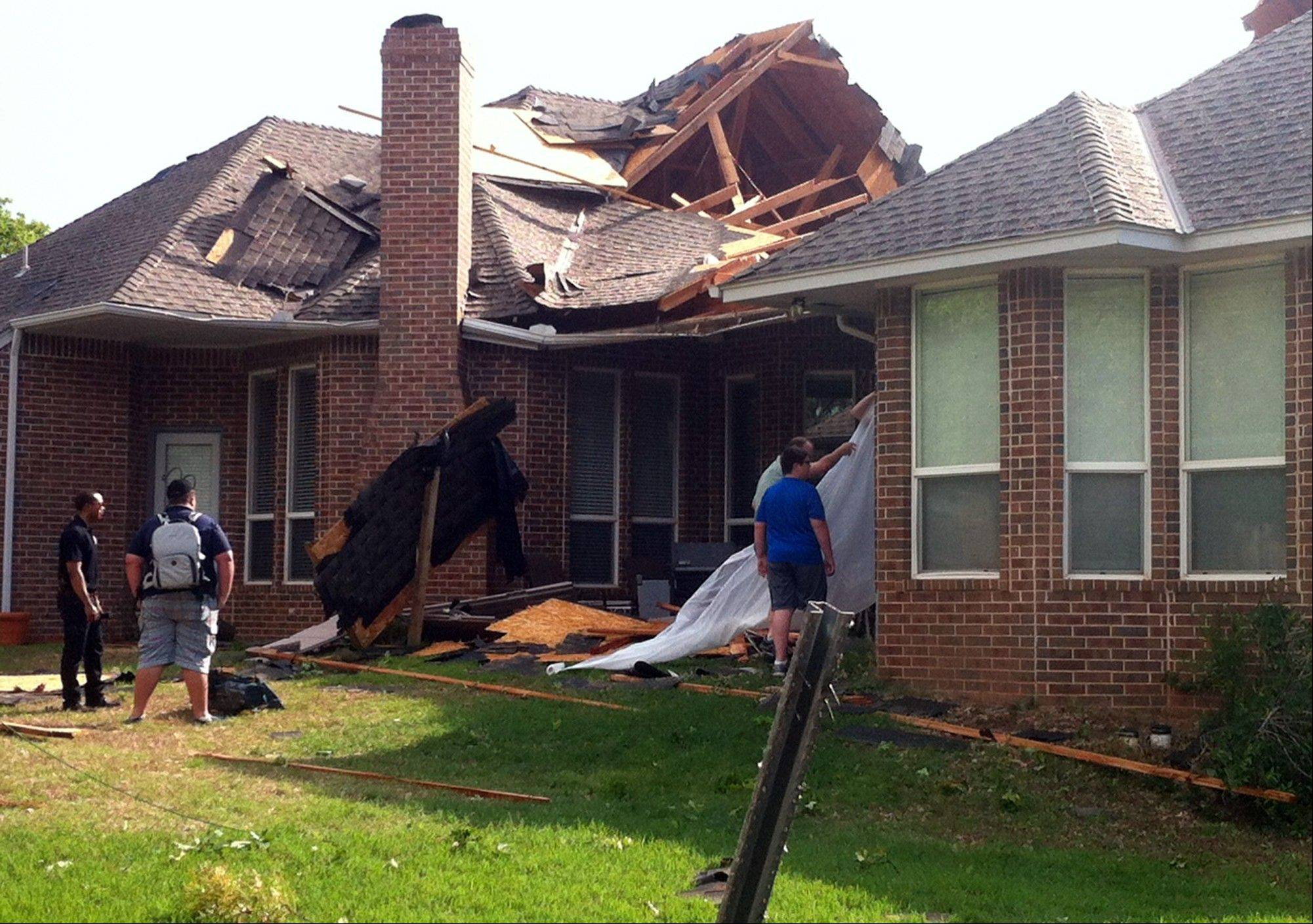 Residents of Edmond, Okla., survey storm damage from a tornado that hit their neighborhood Sunday, May 19, 2013. Forecasters had warned that the middle of the country would see severe weather throughout the weekend.