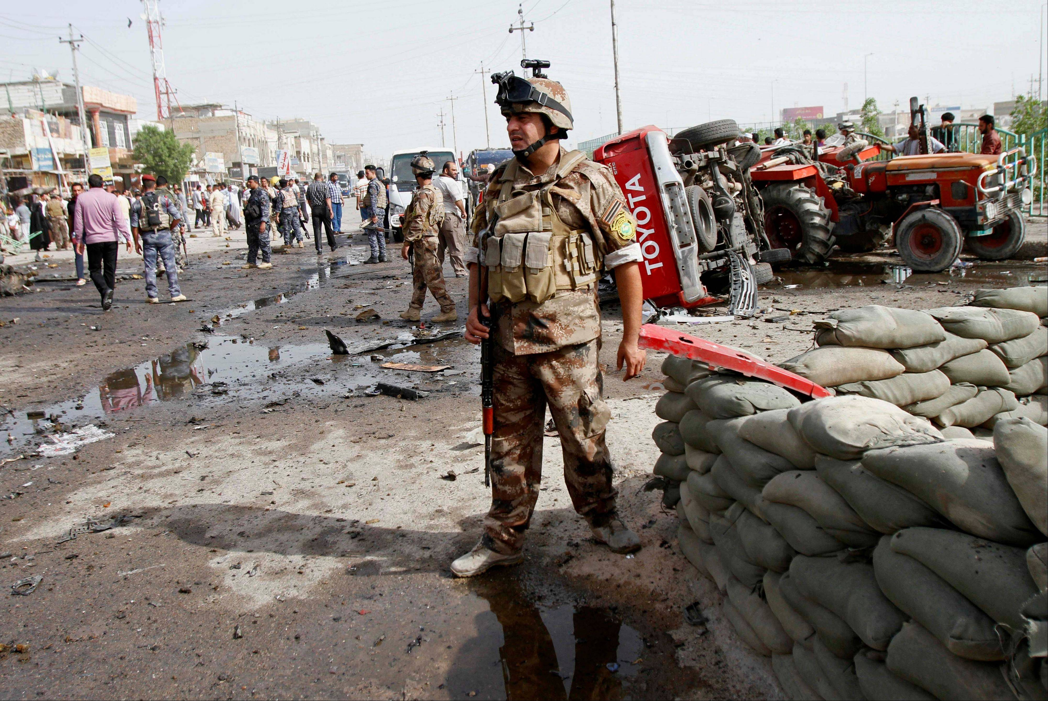 Iraqi security force members inspect the site of a car-bomb attack in Basra, 340 miles southeast of Baghdad, Iraq, Monday. Two car bombings in the southern city of Basra killed and wounded dozens of people, police said.