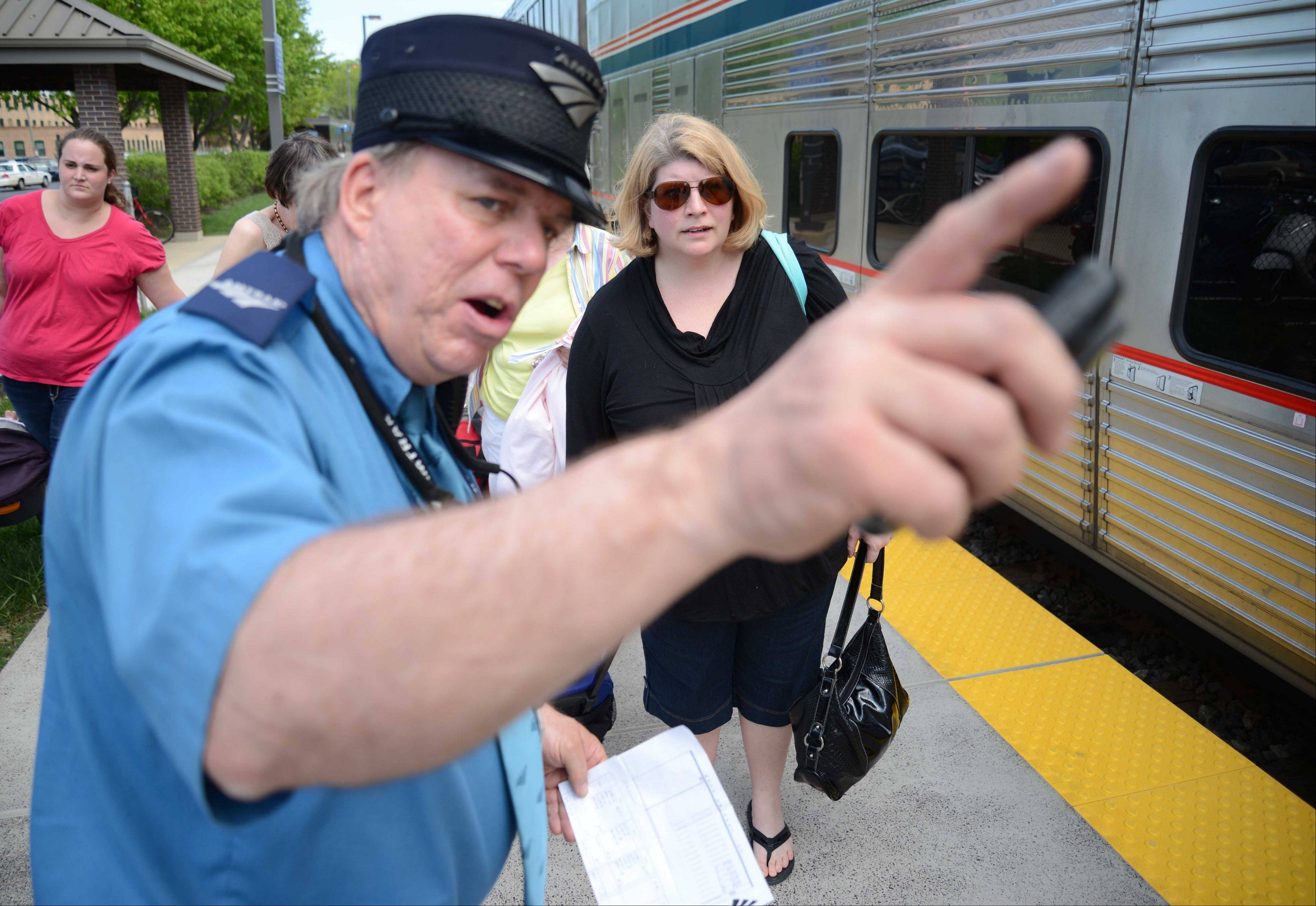 Paul Michna/pmichna@dailyherald.comKevin Crowe, left, helps Jenny Wright of Naperville find her train car on the Amtrak's California Zephyr in Naperville.