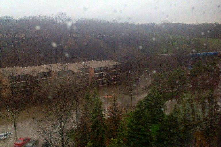 Floodwaters begin overtaking cars April 18, as seen from Debra Schulz's eighth-floor apartment at the Towers at Four Lakes complex in Lisle