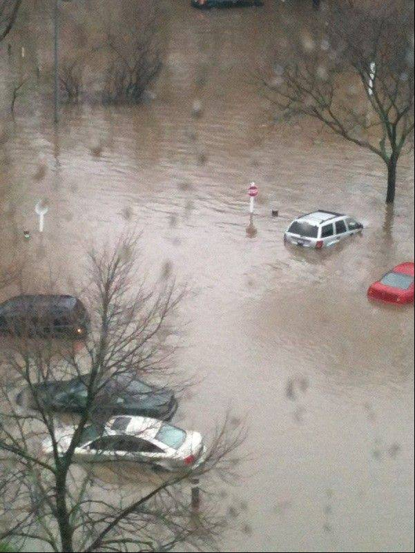 Vehicles parked in front of the Towers at Four Lakes apartments in Lisle take on floodwater April 18.